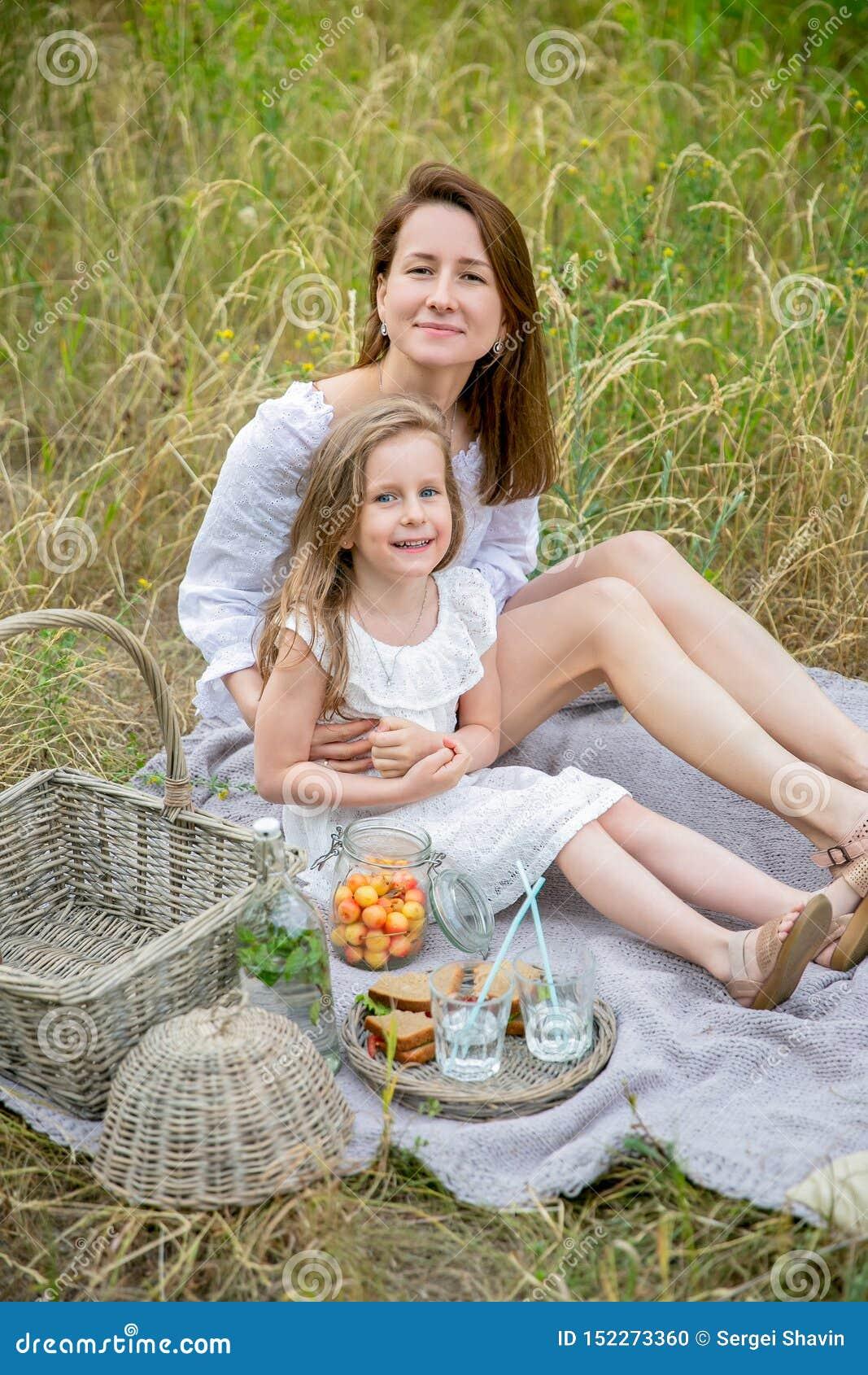 Belle jeune mère et sa petite fille dans la robe blanche ayant l amusement dans un pique-nique un jour d été Ils se reposent sur