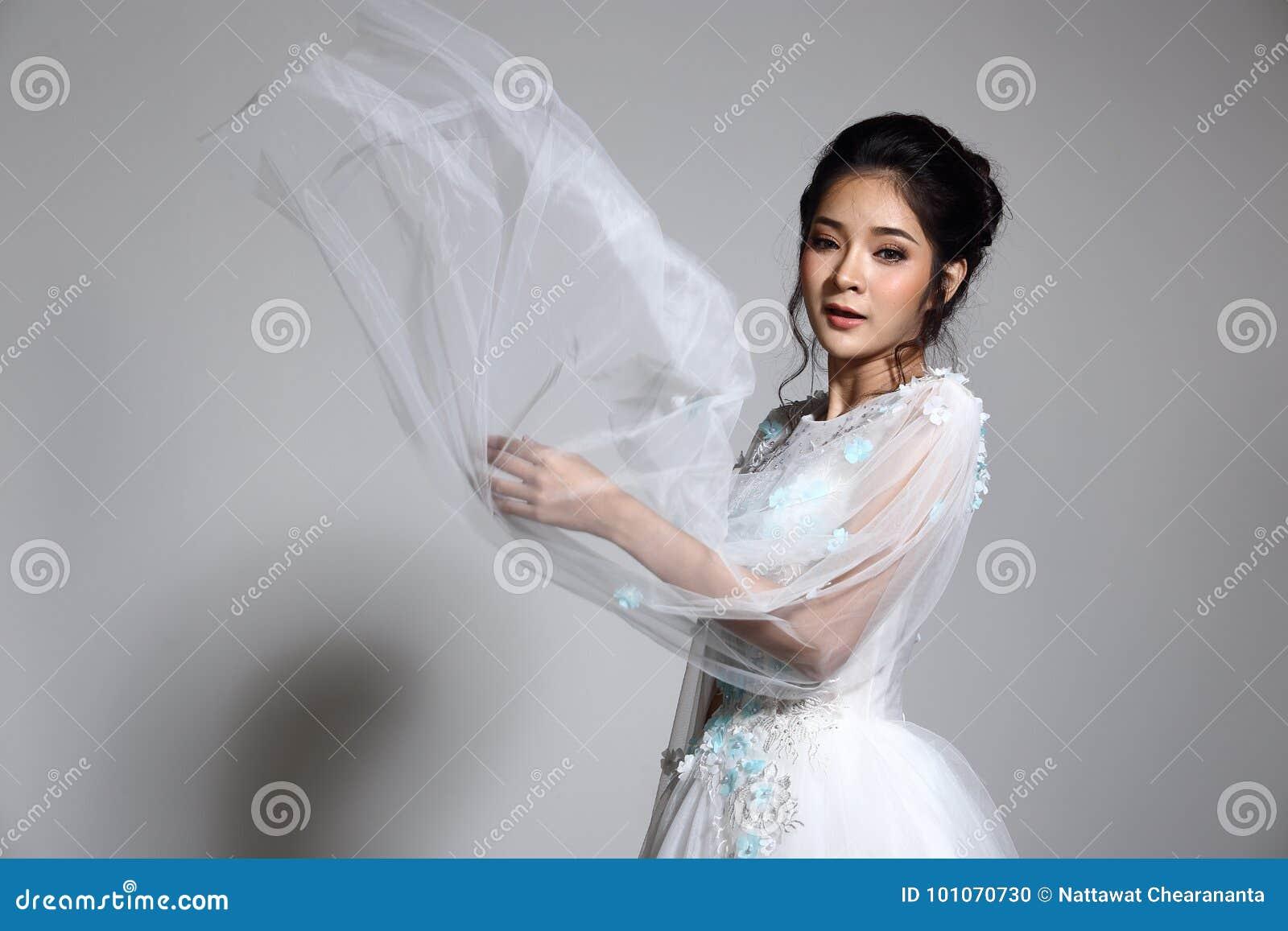 Belle belle jeune mariée asiatique de femme dans la robe blanche W de robe de mariage