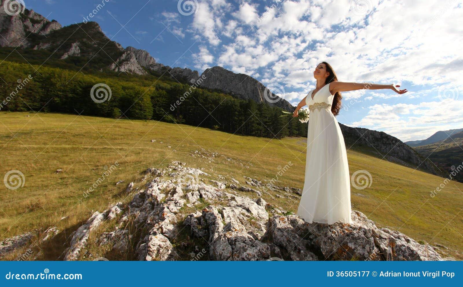 Belle jeune mariée avec des bras en nature