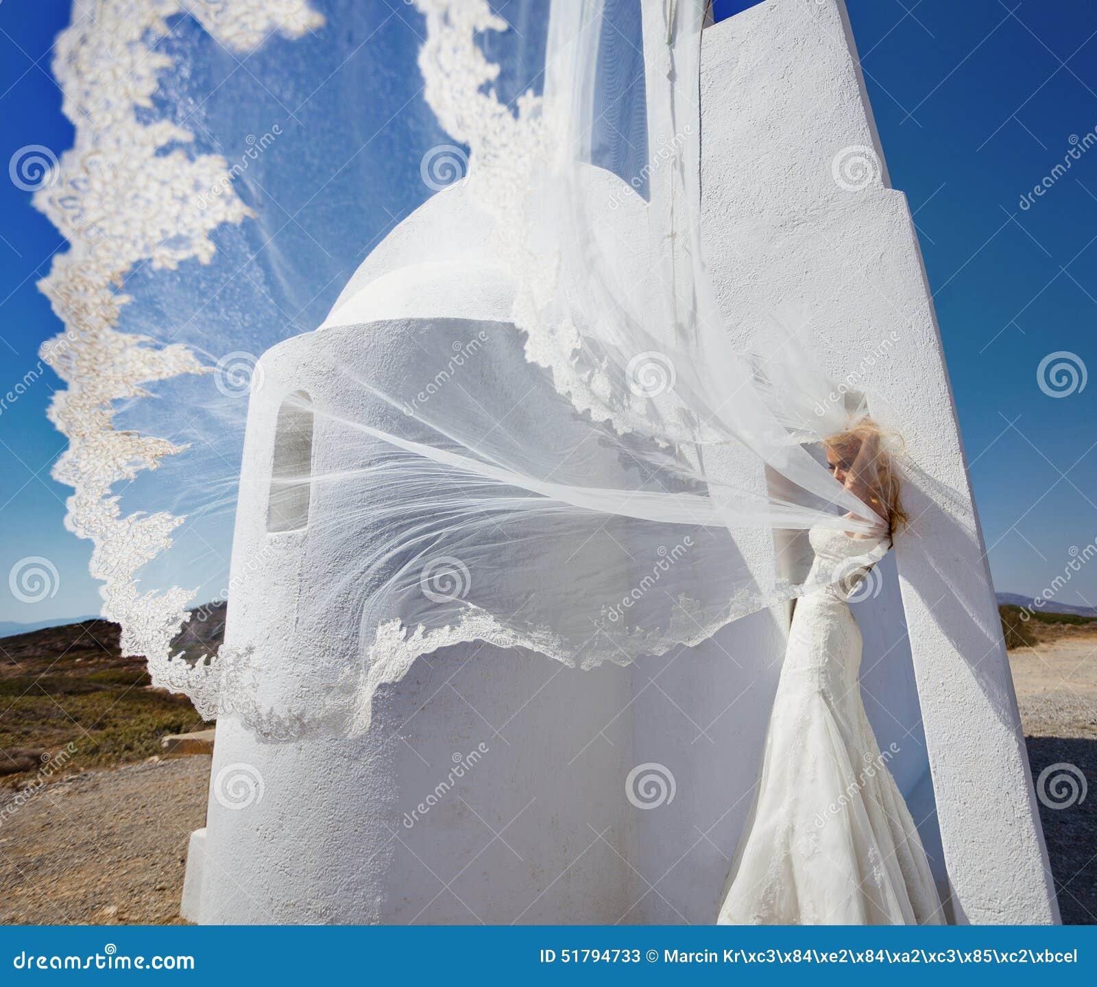 Belle jeune mariée dans une robe de mariage en Grèce avec un long voile
