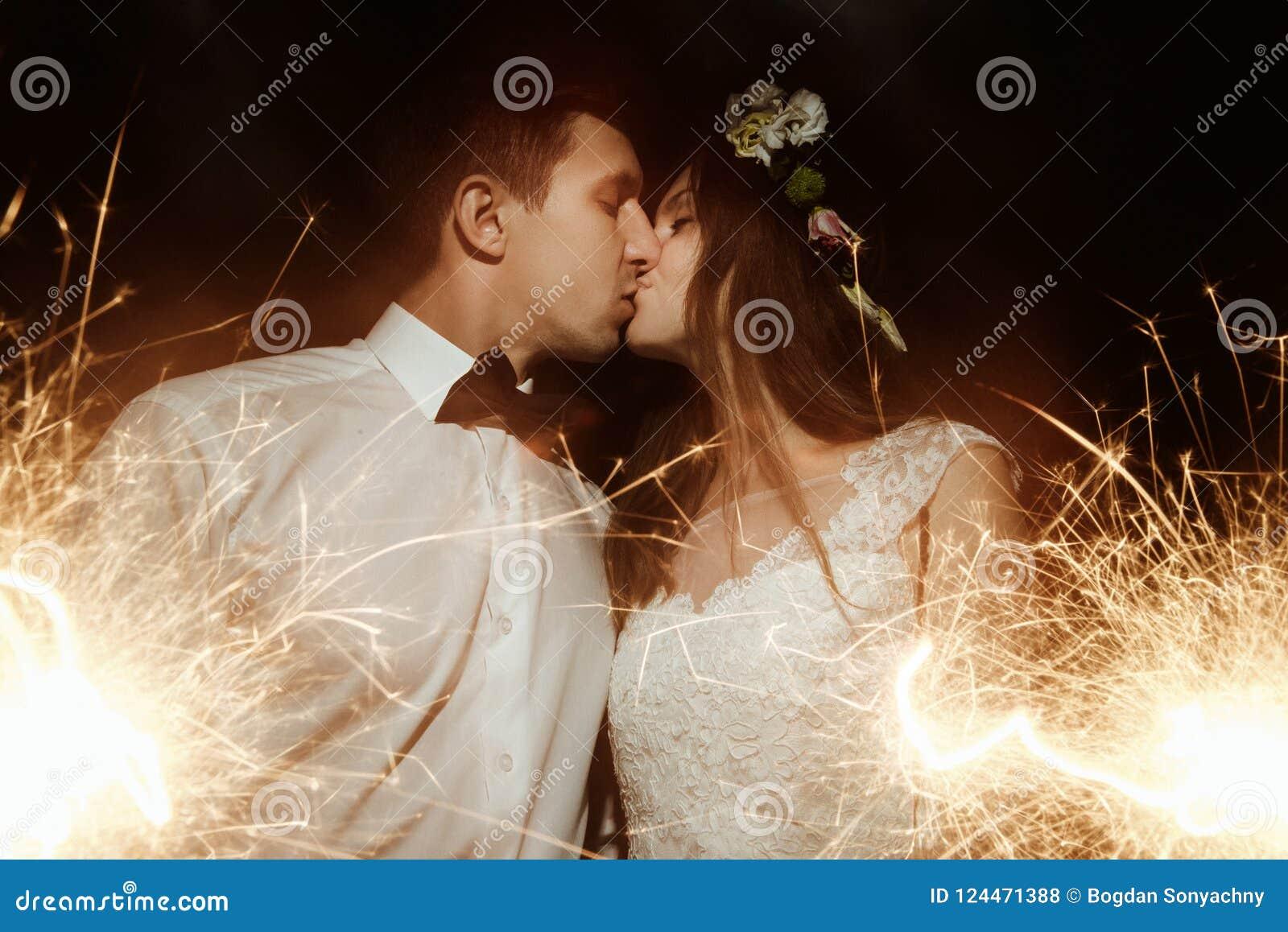 Belle jeune mariée heureuse et marié élégant élégant tenant le feu d artifice