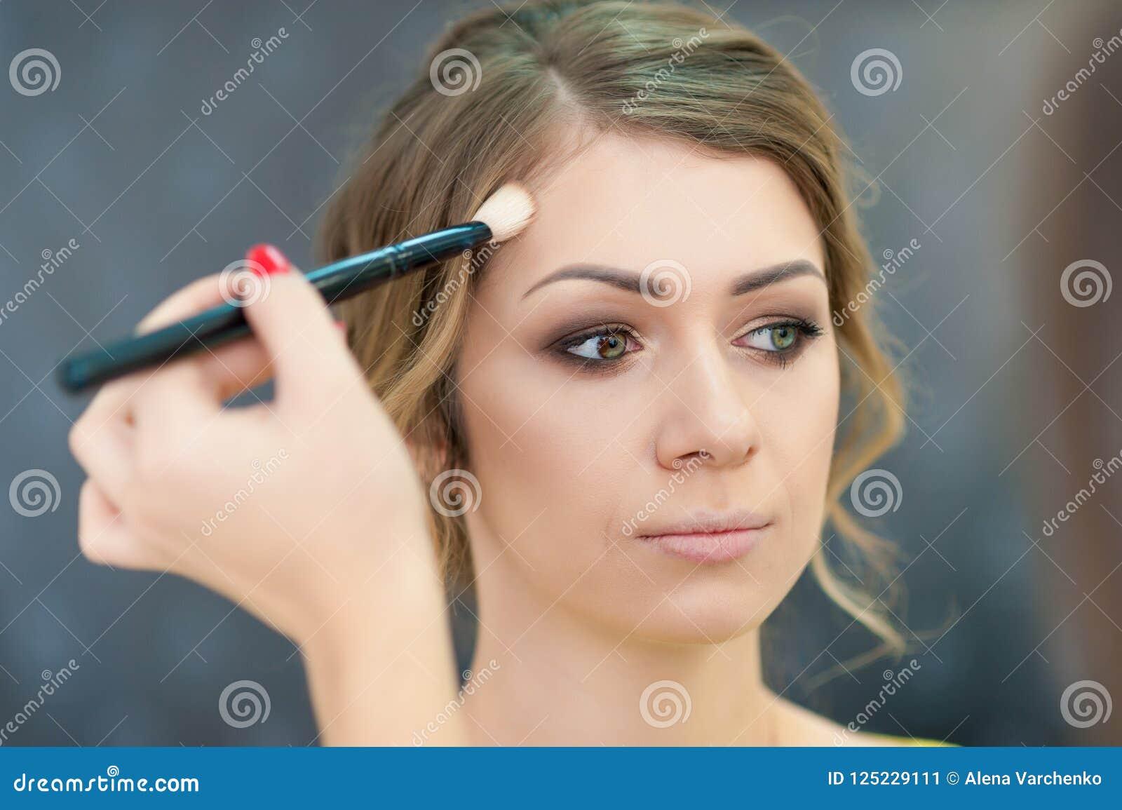 Belle jeune mariée s appliquant épousant le maquillage dans le salon