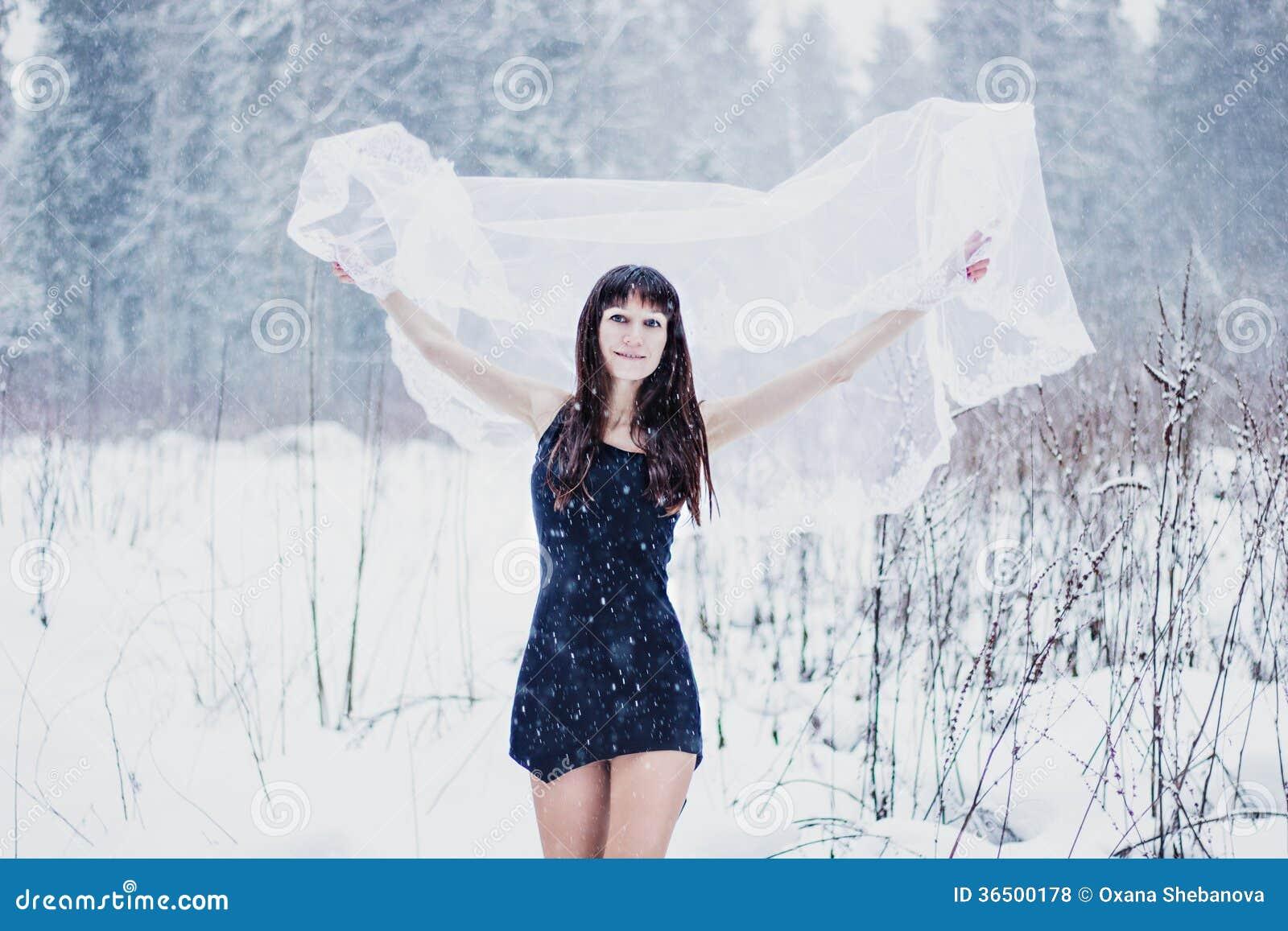 Belle jeune mariée sous le voile sur le fond blanc de neige