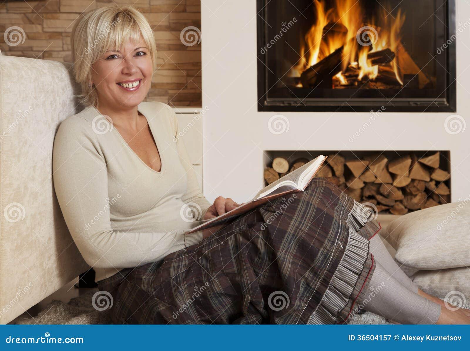 Belle lecture de femme par la cheminée à la maison