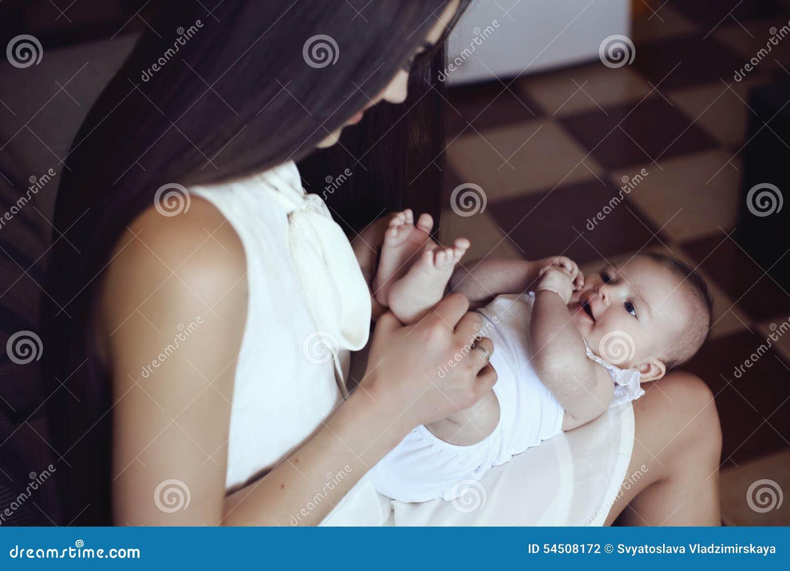 Belle mère avec les cheveux foncés luxueux et son petit bébé