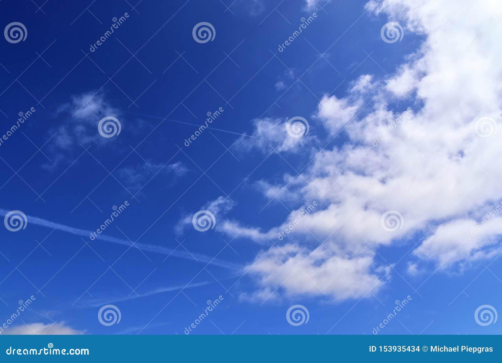 Belle nuvole lanuginose bianche su un cielo blu profondo