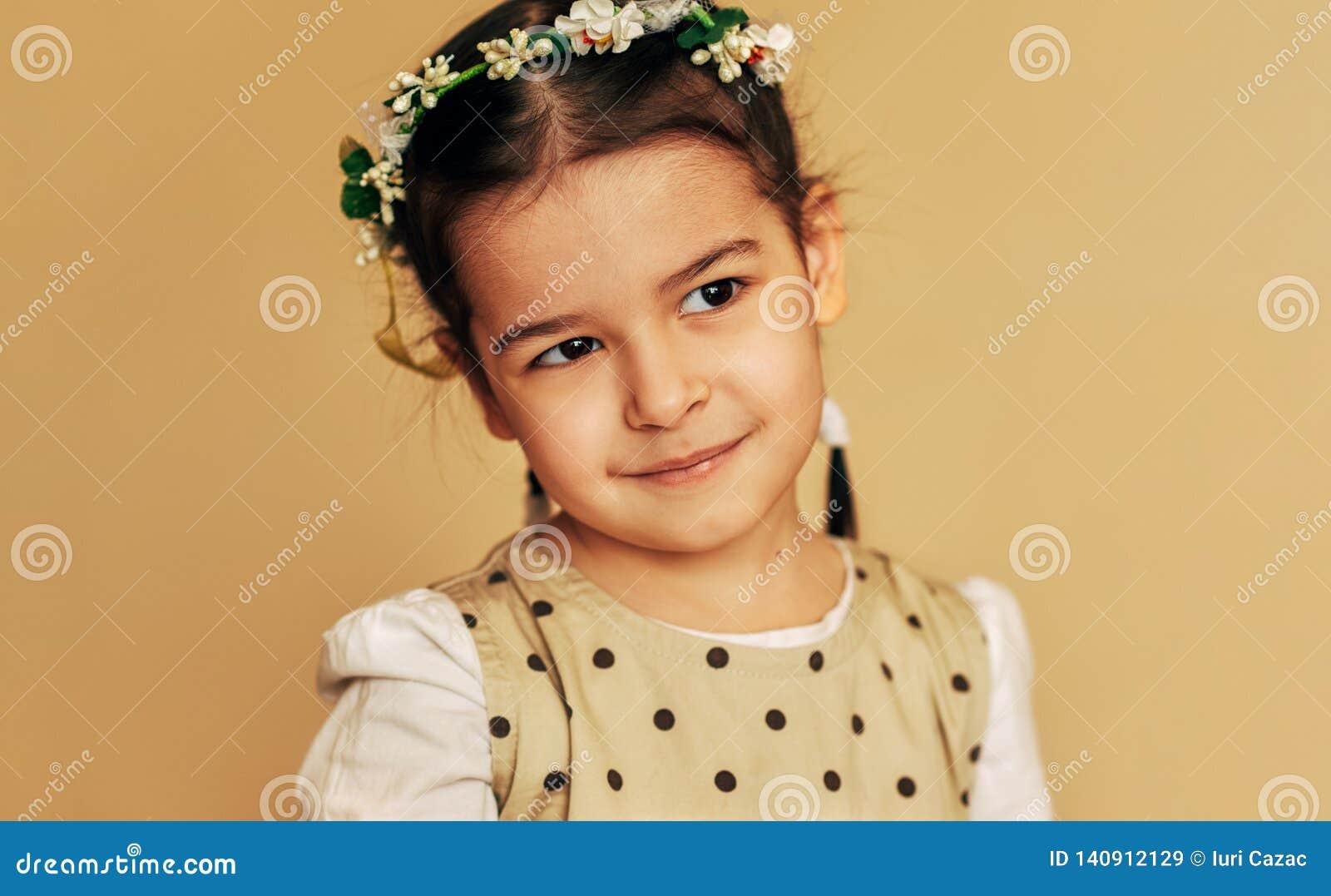 Belle petite fille avec des fleurs sur ses cheveux, posant pour la photo de famille dans le studio Sourire adorable heureux de fi
