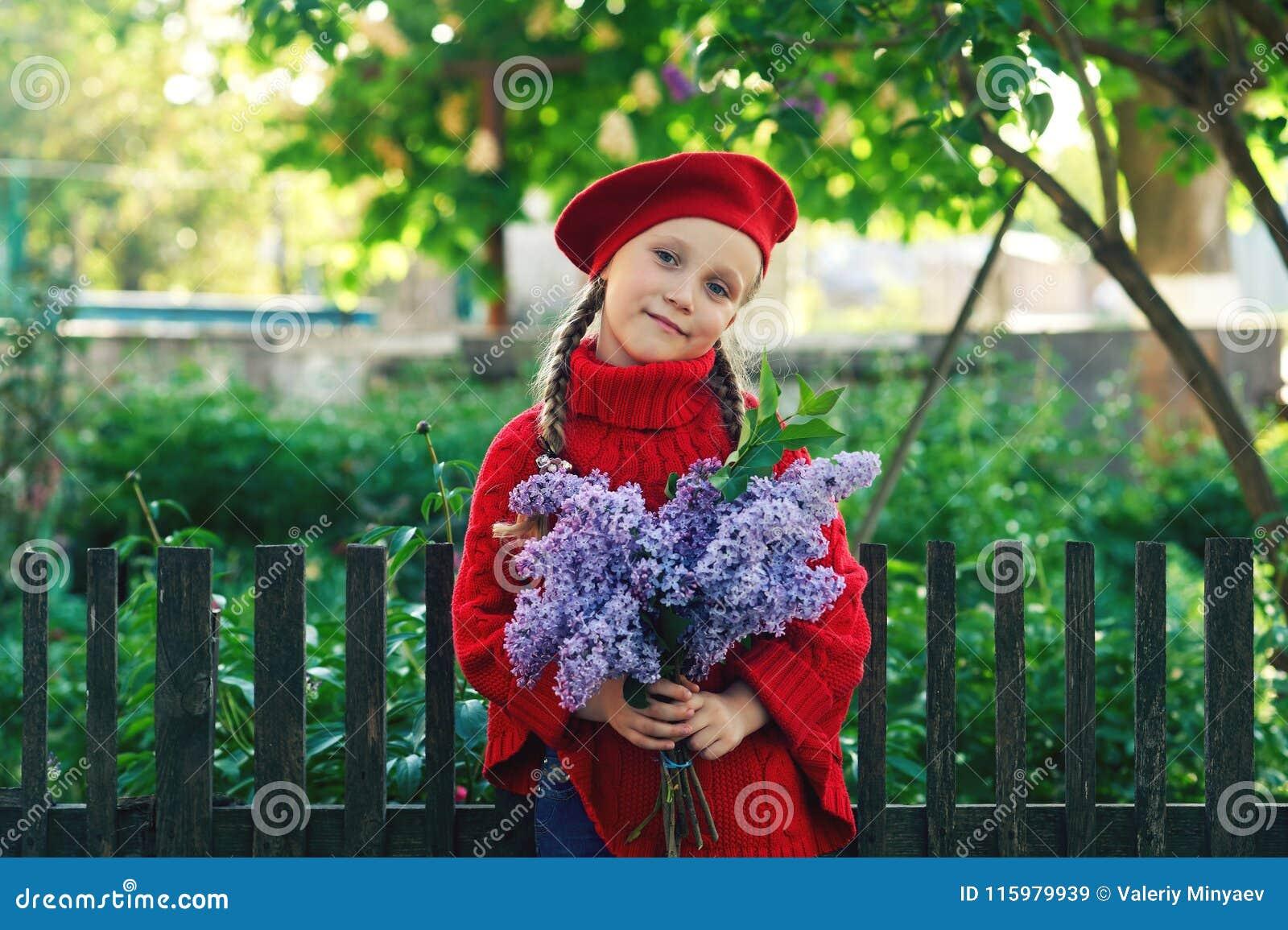 Belle petite fille avec un bouquet des lilas