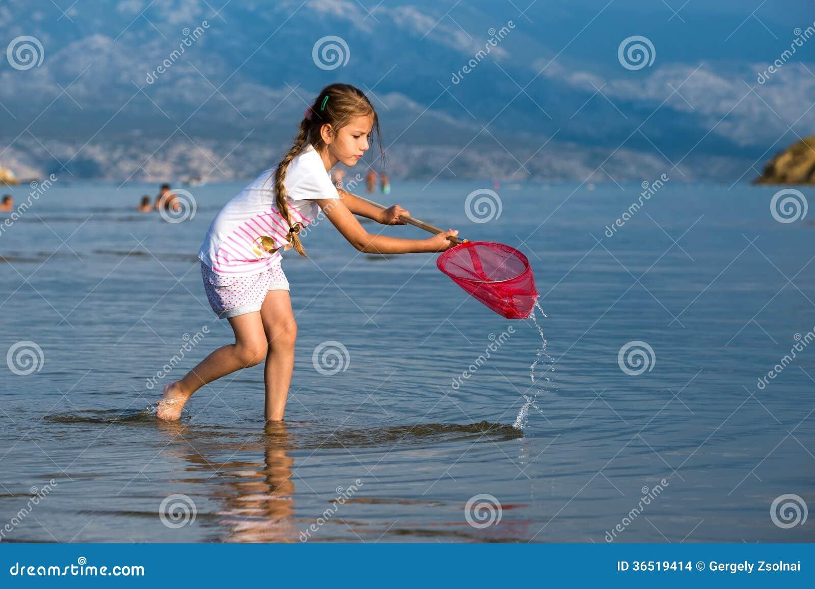 Belle petite fille sur les poissons de plage