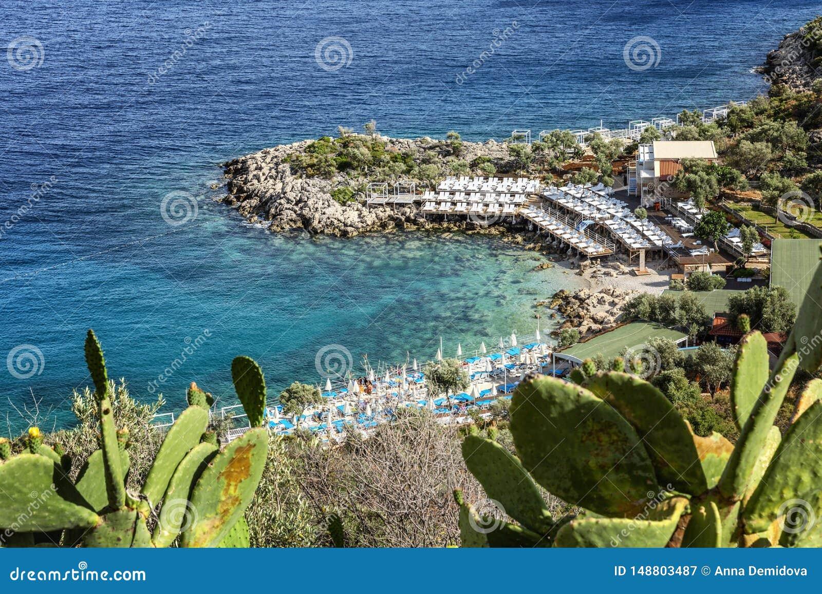 Belle plage sur une plage rocheuse avec des canapés et des parapluies du soleil Horizontal magnifique
