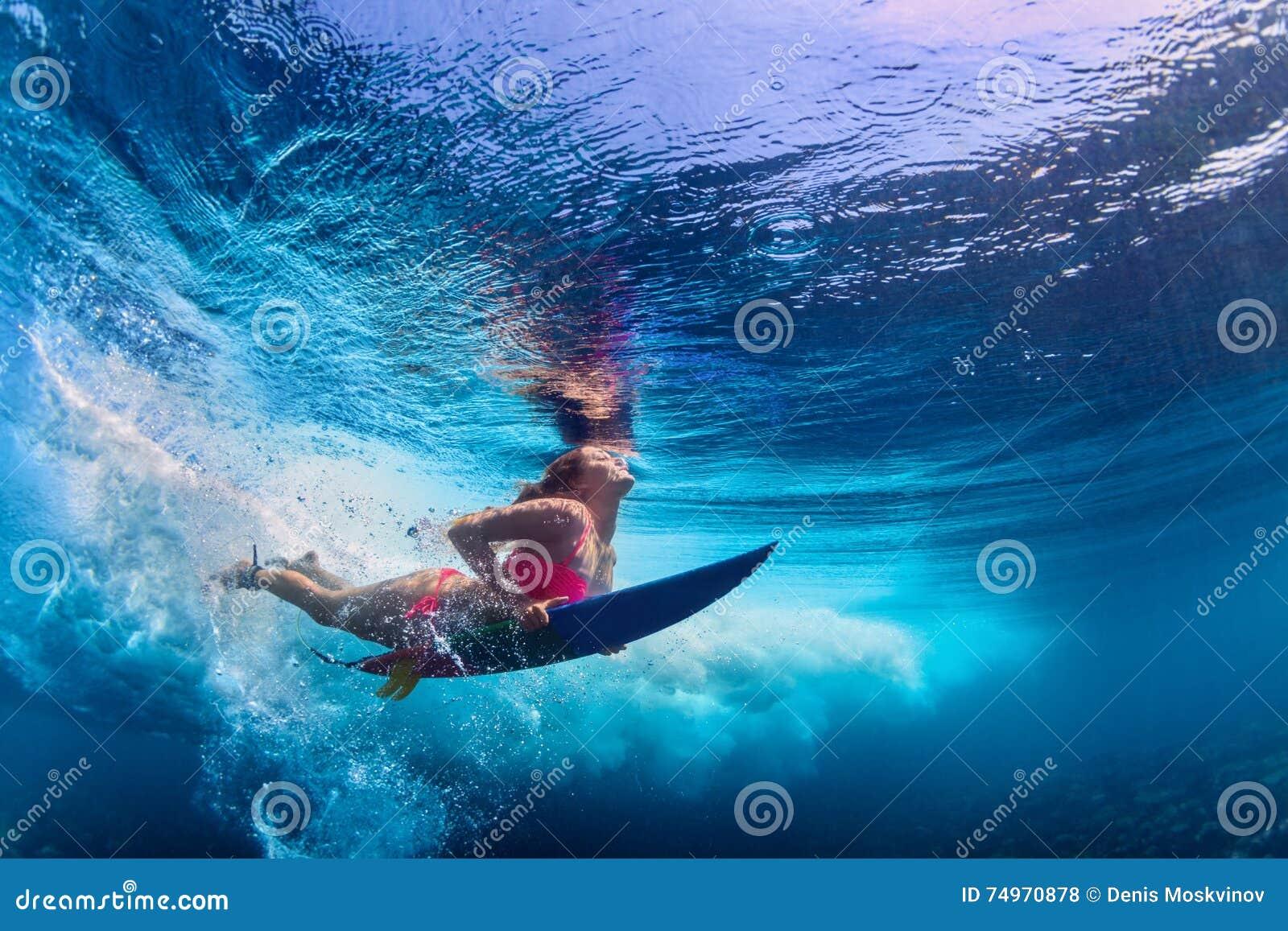 Belle plongée de fille de surfer sous l eau avec le panneau de ressac