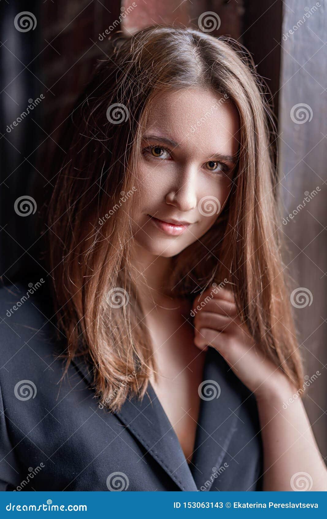 Belle position de jeune femme à la fenêtre dans une veste noire