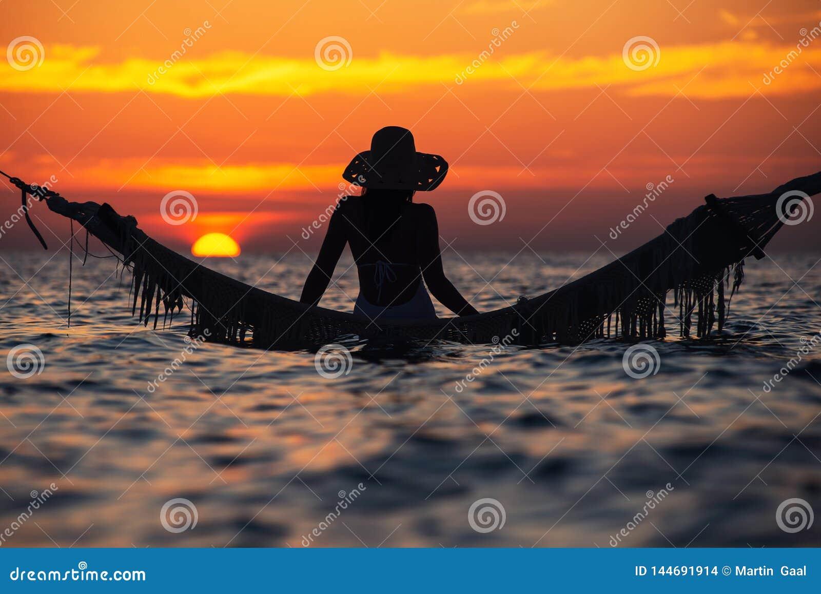 Belle silhouette de jeune femme avec l oscillation posant en mer sur le coucher du soleil, paysage romantique maldivien