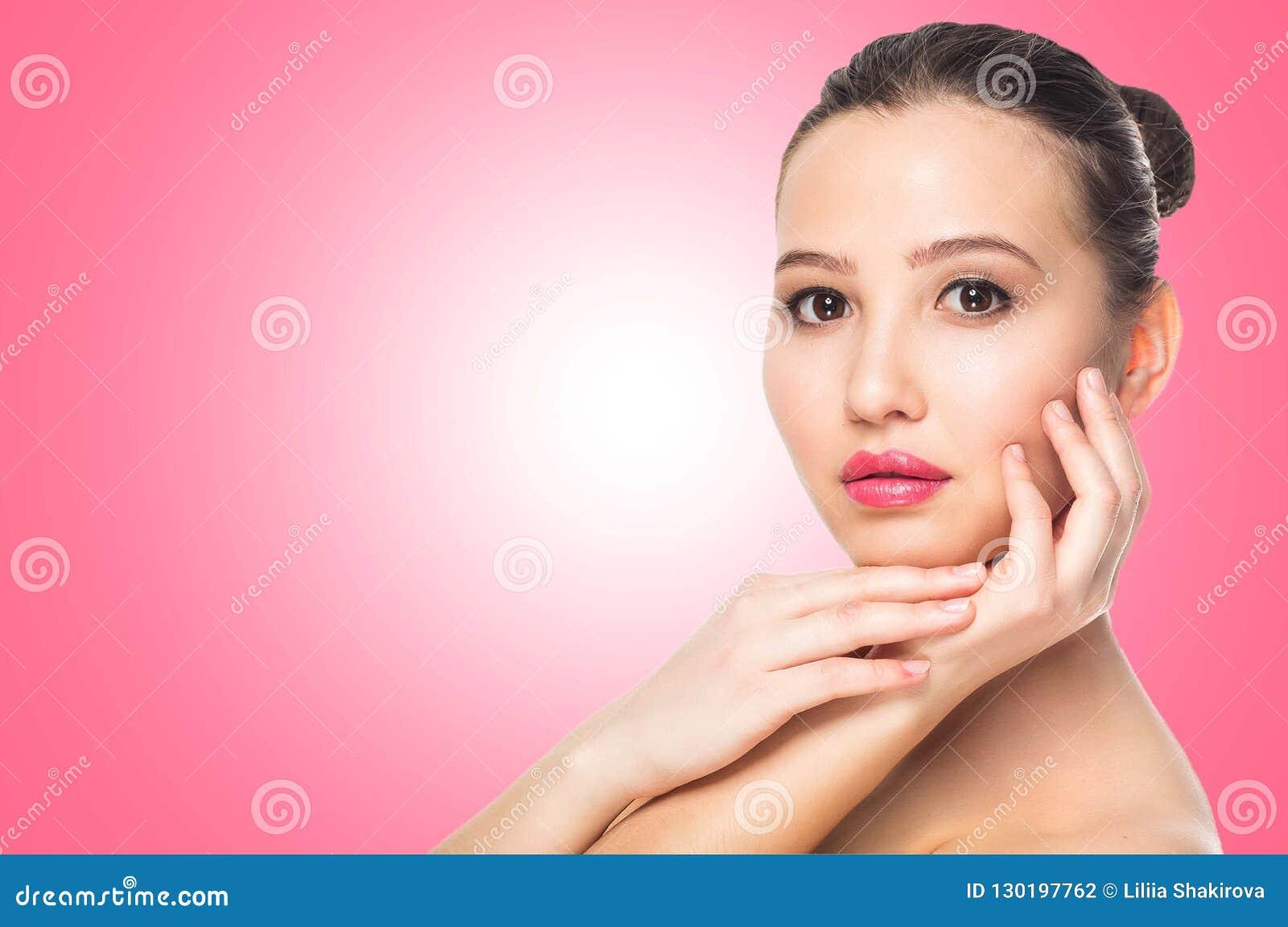 Belle station thermale de femme de brune avec la peau propre, maquillage naturel sur le fond rose avec l espace de copie