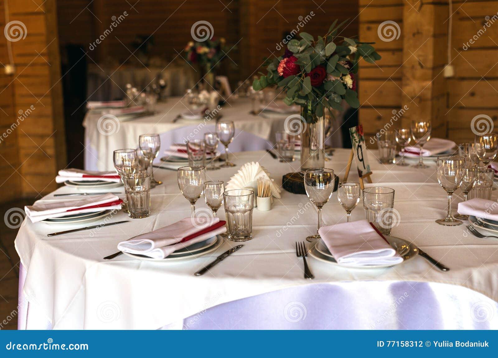 Belle table décorée élégante avec les ustensiles, vases de fleur