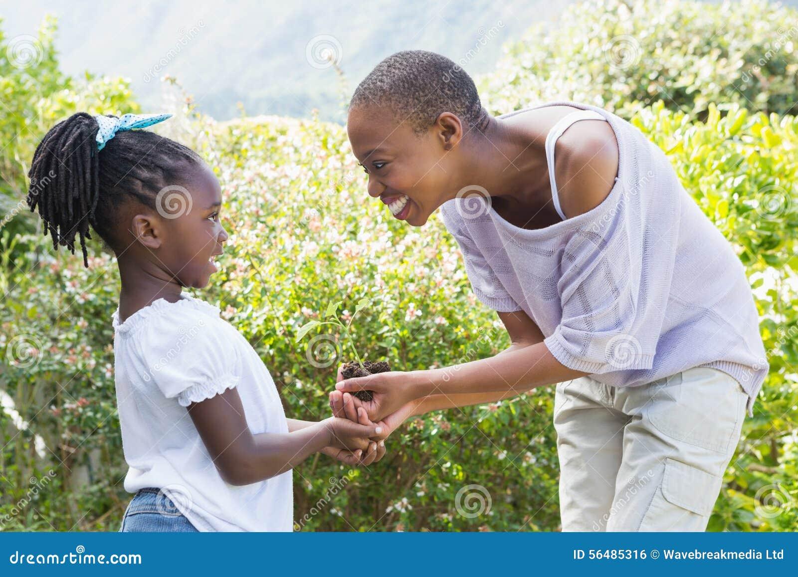 Belle usine de mère de sourire heureuse une fleur avec sa fille