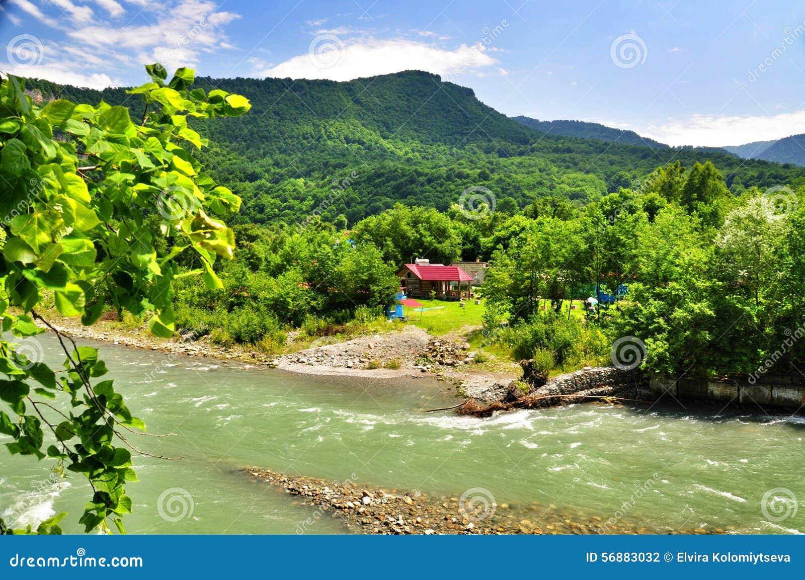Belle viste delle montagne di Caucaso e di piccolo villaggio sulle banche del fiume