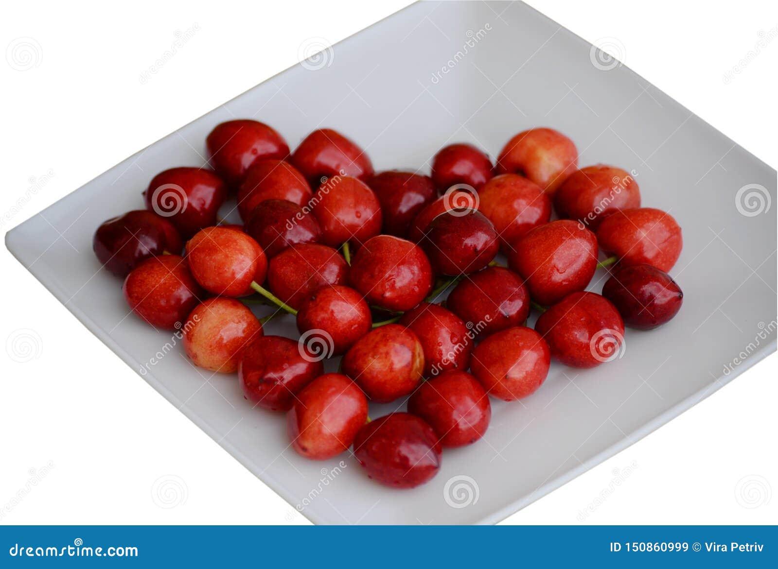 Belles cerises rouges humides sous forme de coeur d un plat carré blanc