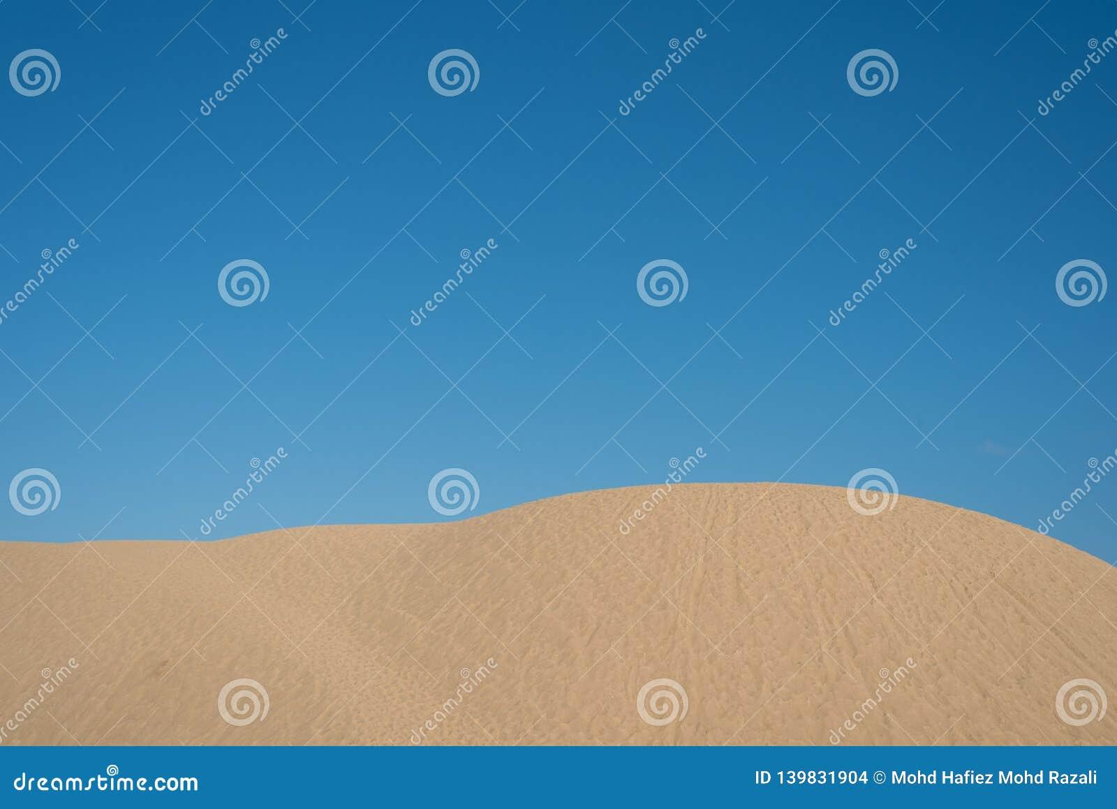 Belles dunes de sable sur le fond lumineux de ciel bleu