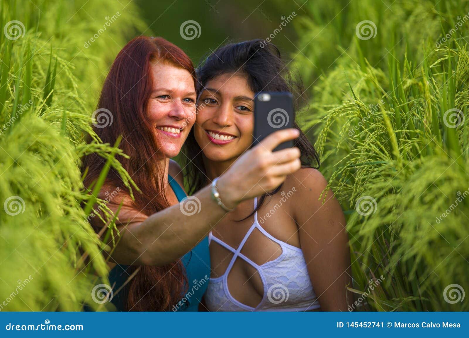 Belles femmes de touristes prenant ? amies le selfie ainsi que le t?l?phone portable dans appr?cier de sourire de paysage de natu