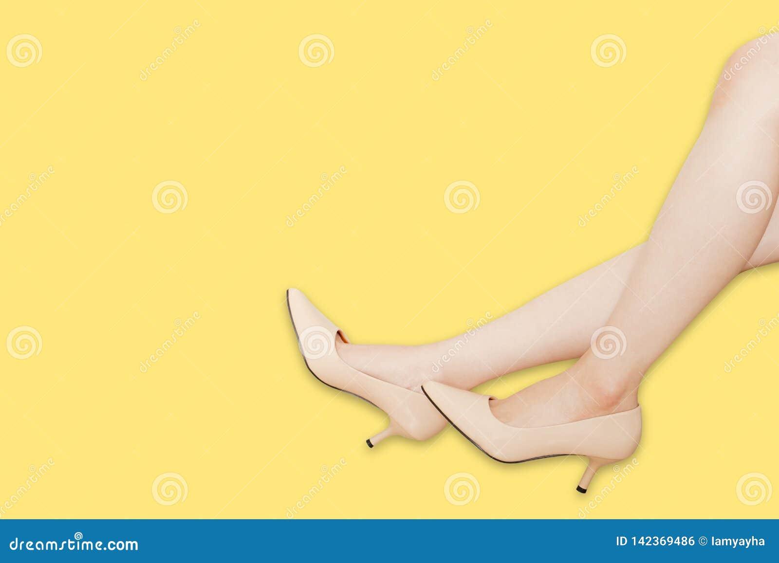 Belles jambes asiatiques de femme portant les chaussures beiges de talons hauts d été d isolement sur le fond jaune avec le chemi