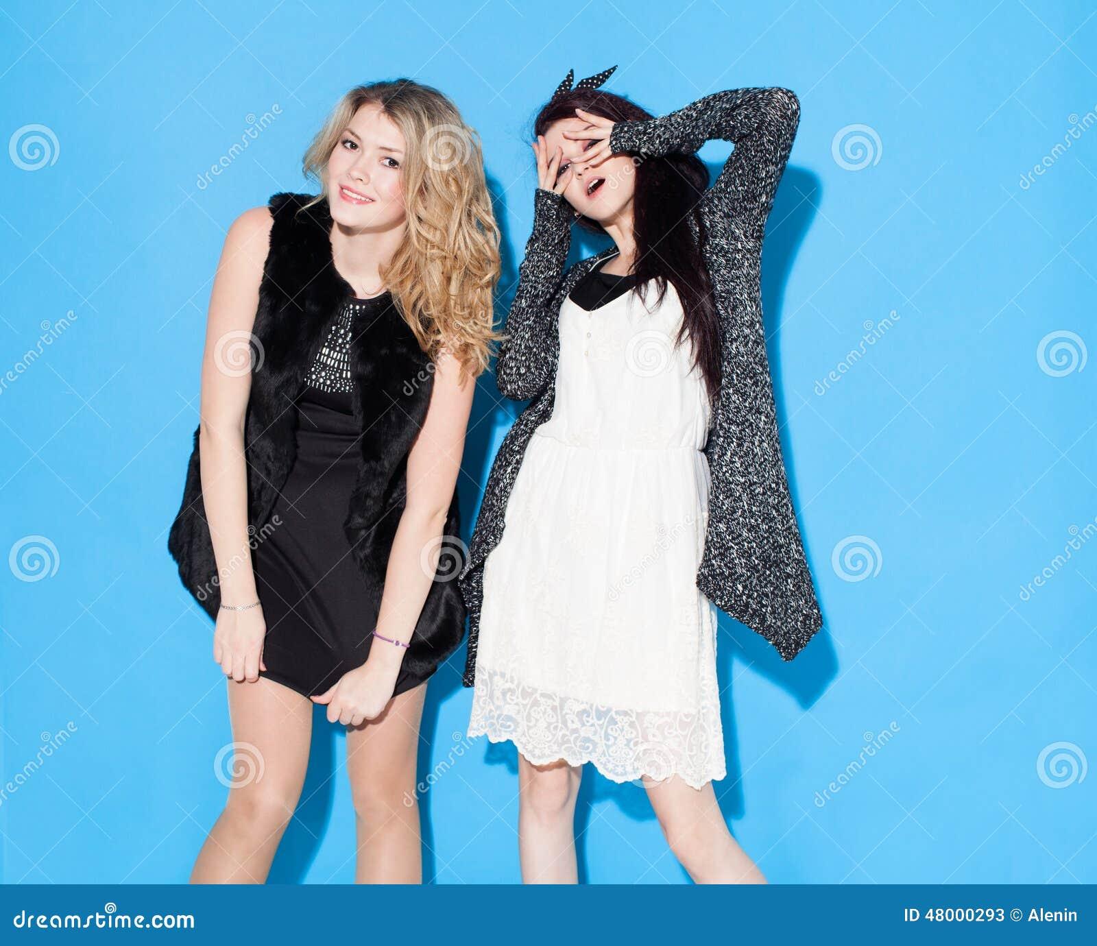 Belles jeunes amies à la mode se tenant ensemble près d un fond bleu Avoir drôle et pose regarder l appareil-photo Indo