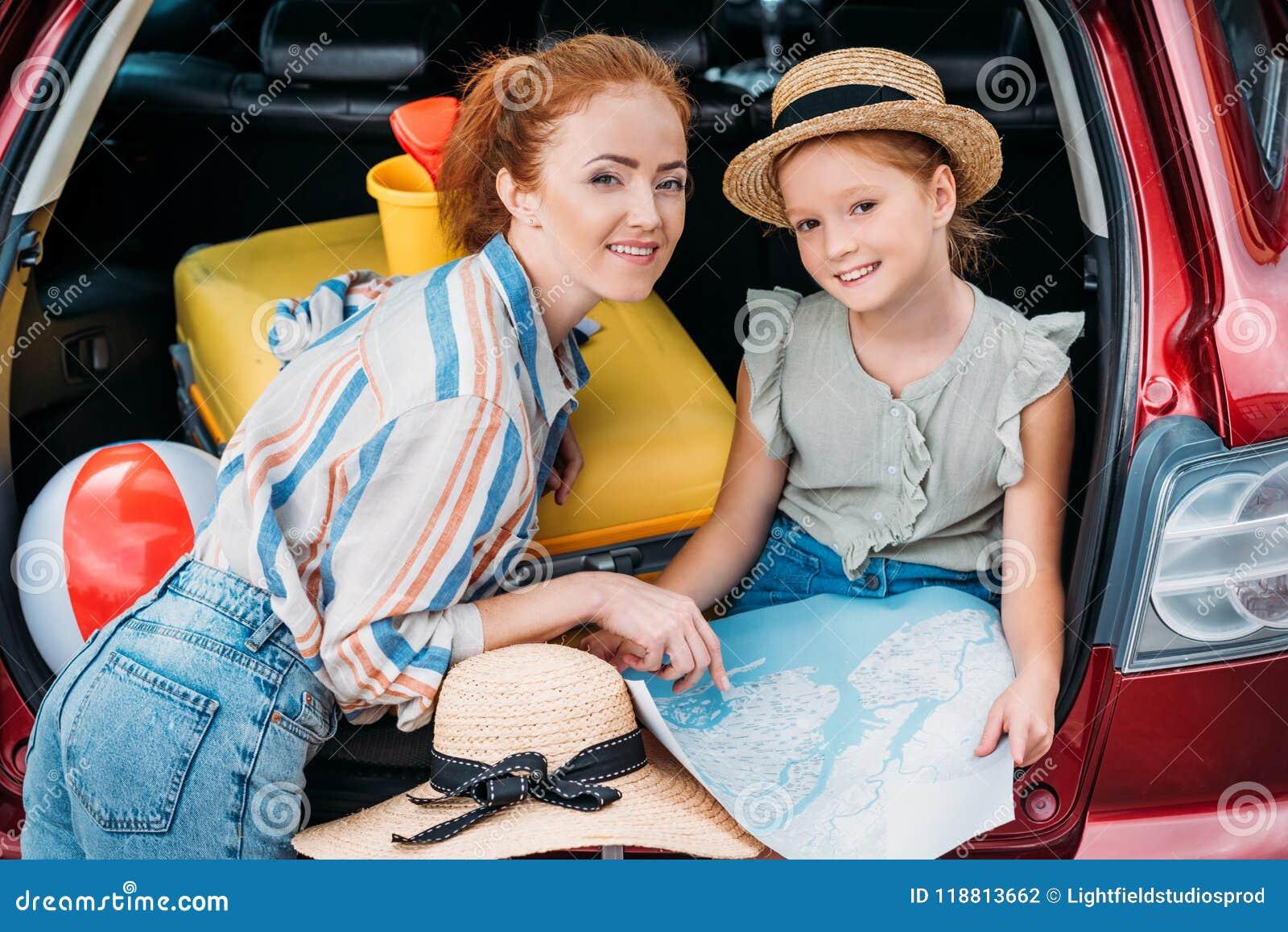Belles jeunes mère et fille dans le tronc de voiture prêt