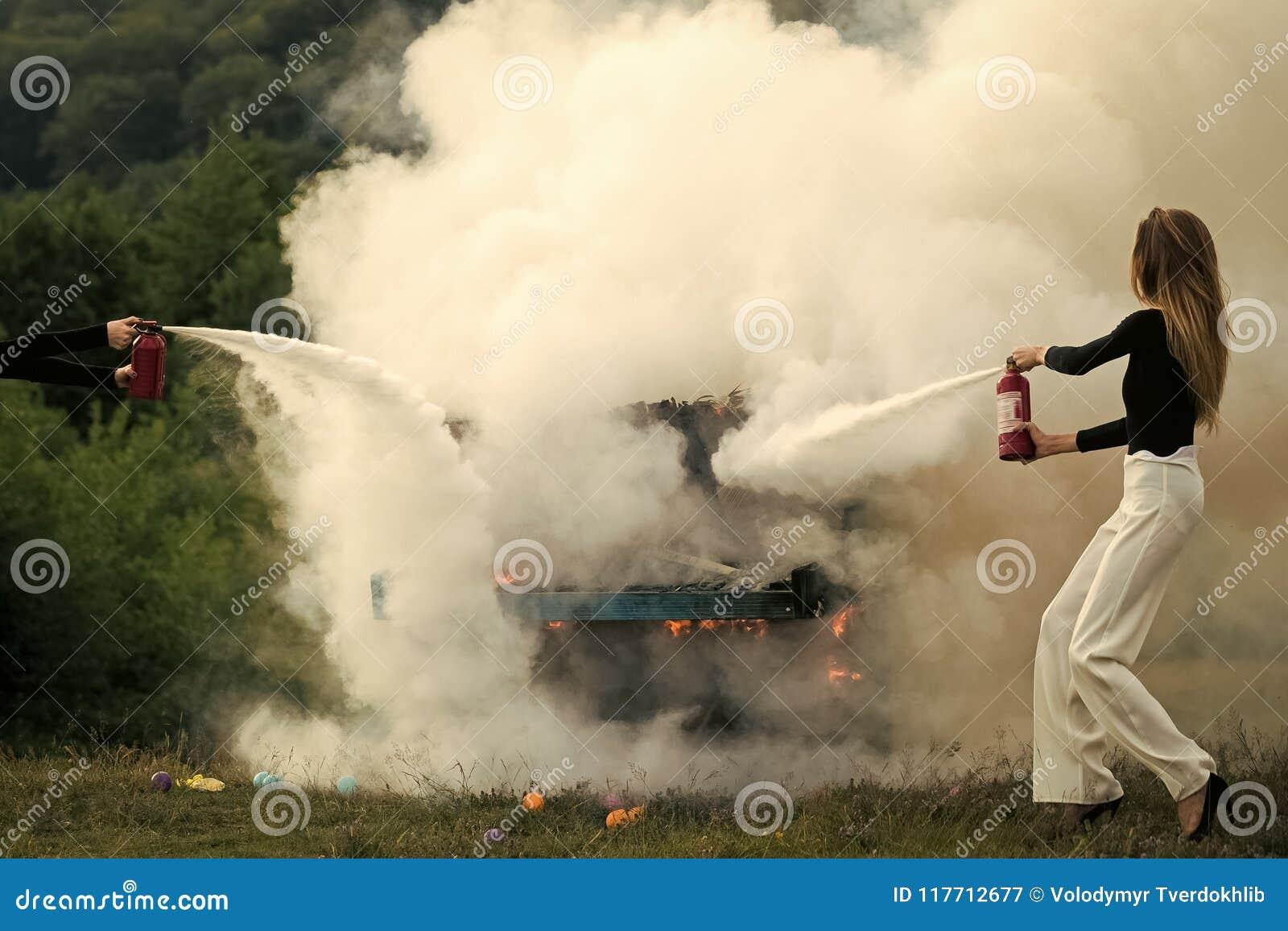 Belleza de la cara de la mujer Fuego y humo en el instrumento del grunge Lucha contra el fuego de la muchacha con el extintor Muj