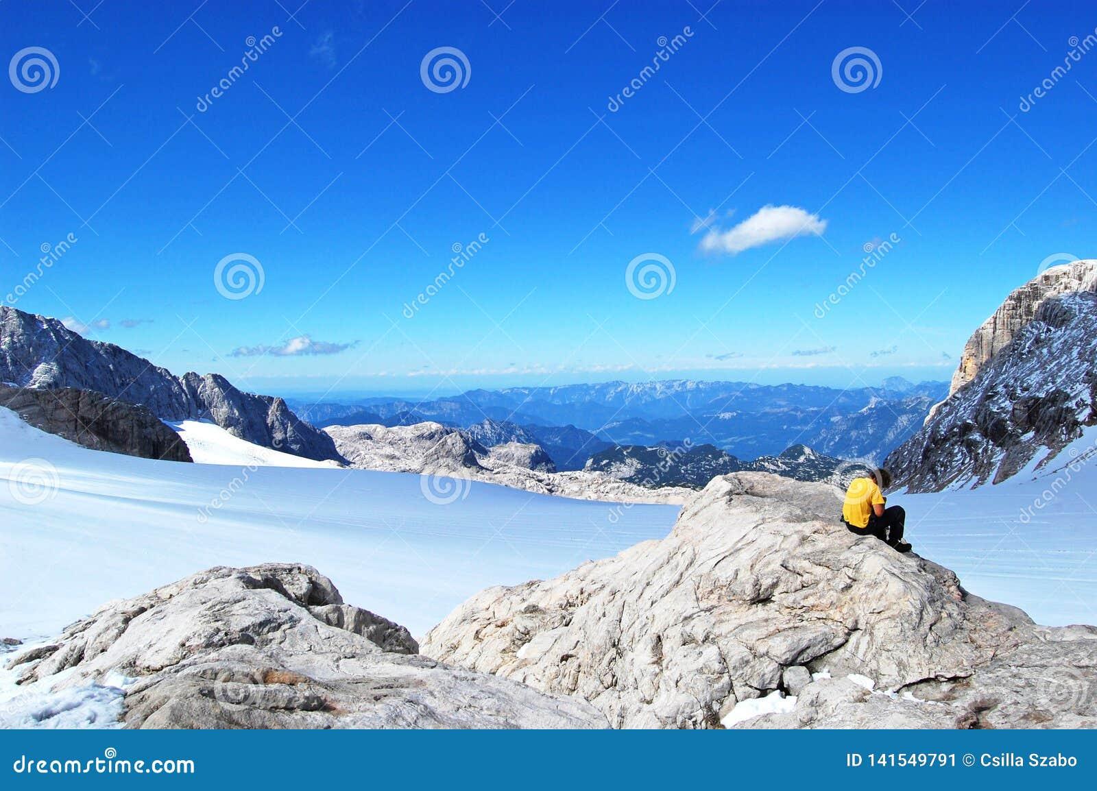 Belleza de la naturaleza, paisaje alpino que sorprende con las rocas, caminando en soporte, cielo azul, nubes, nieve, sol