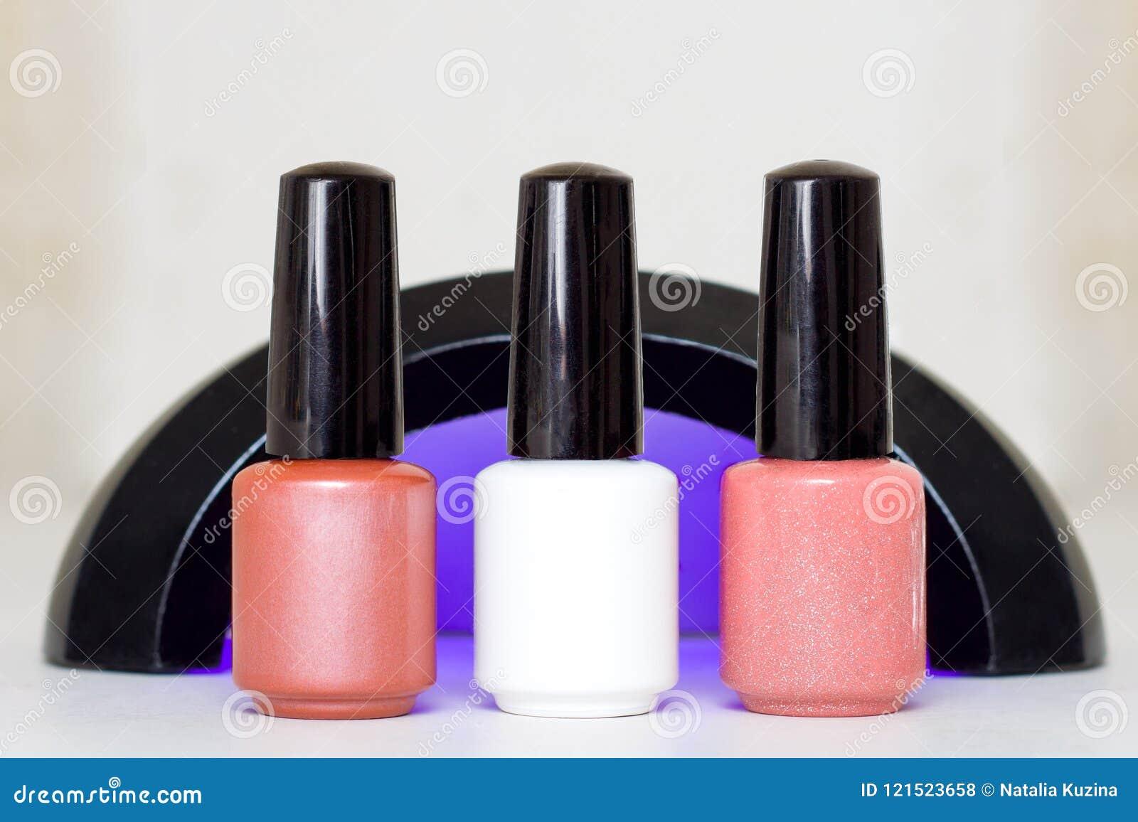 Belleza, moda y clavo Art Concept Manicure el esmalte de uñas beige blanco rosado ultravioleta de la lámpara de las herramientas