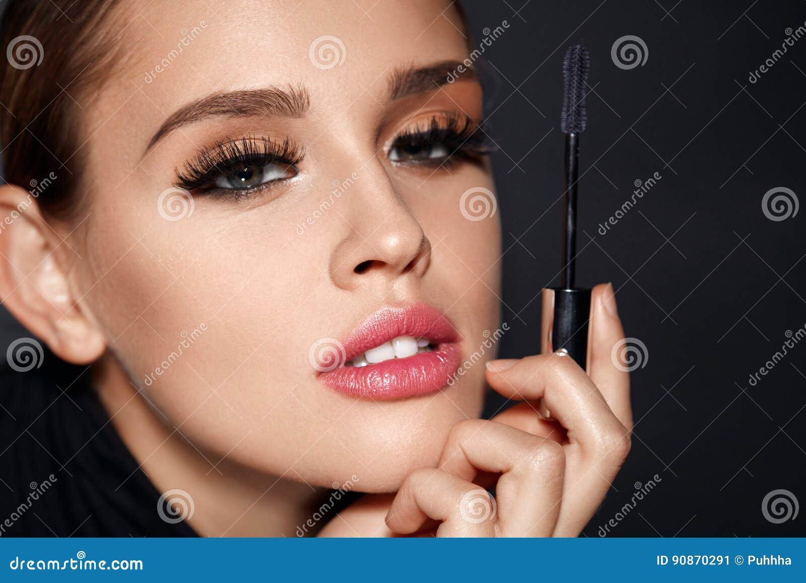 Belleza Mujer con el cepillo hermoso de la cara y del rimel a disposición