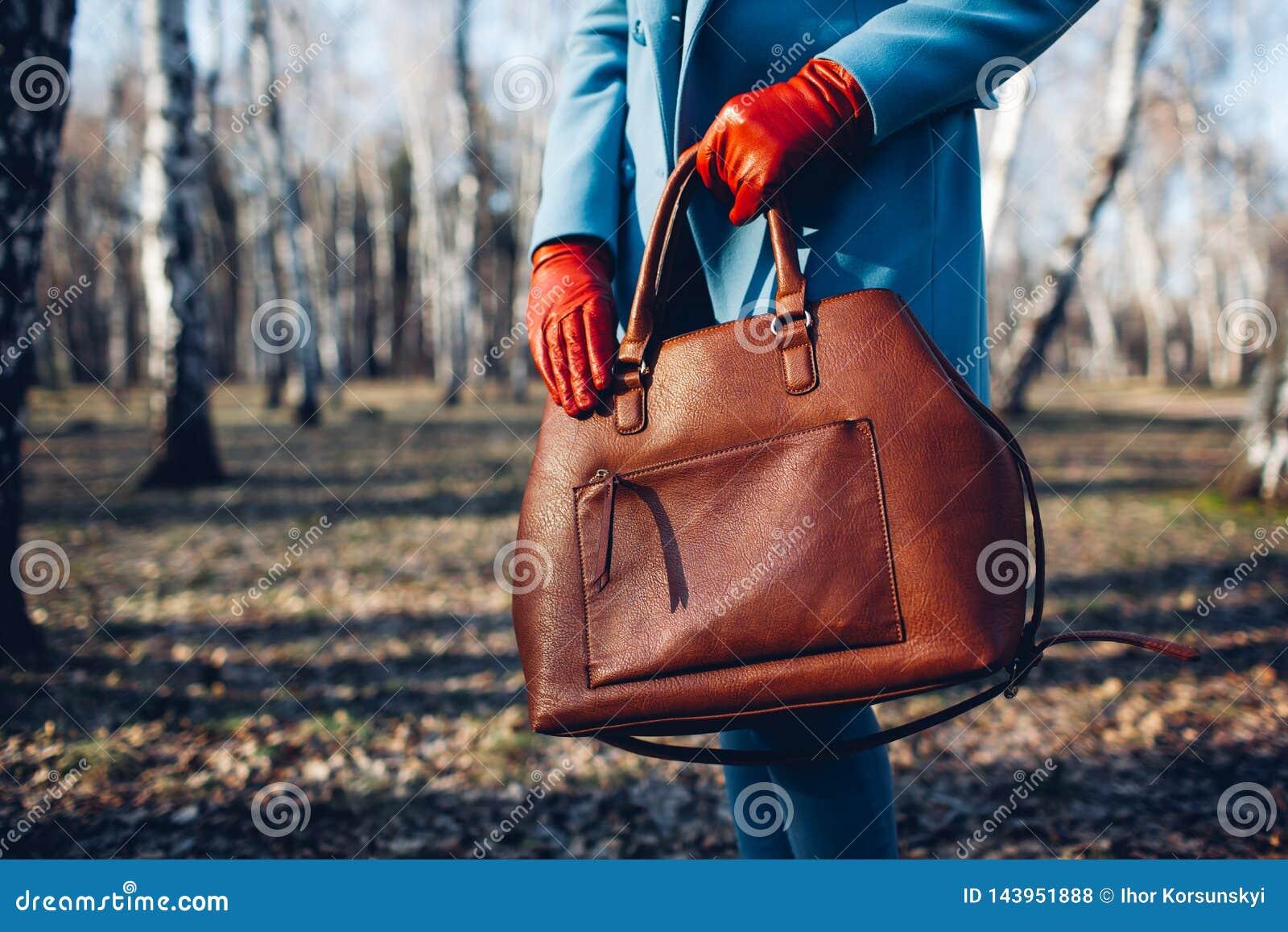 Belleza y moda Mujer de moda elegante que lleva el vestido brillante que sostiene el bolso marr?n del bolso