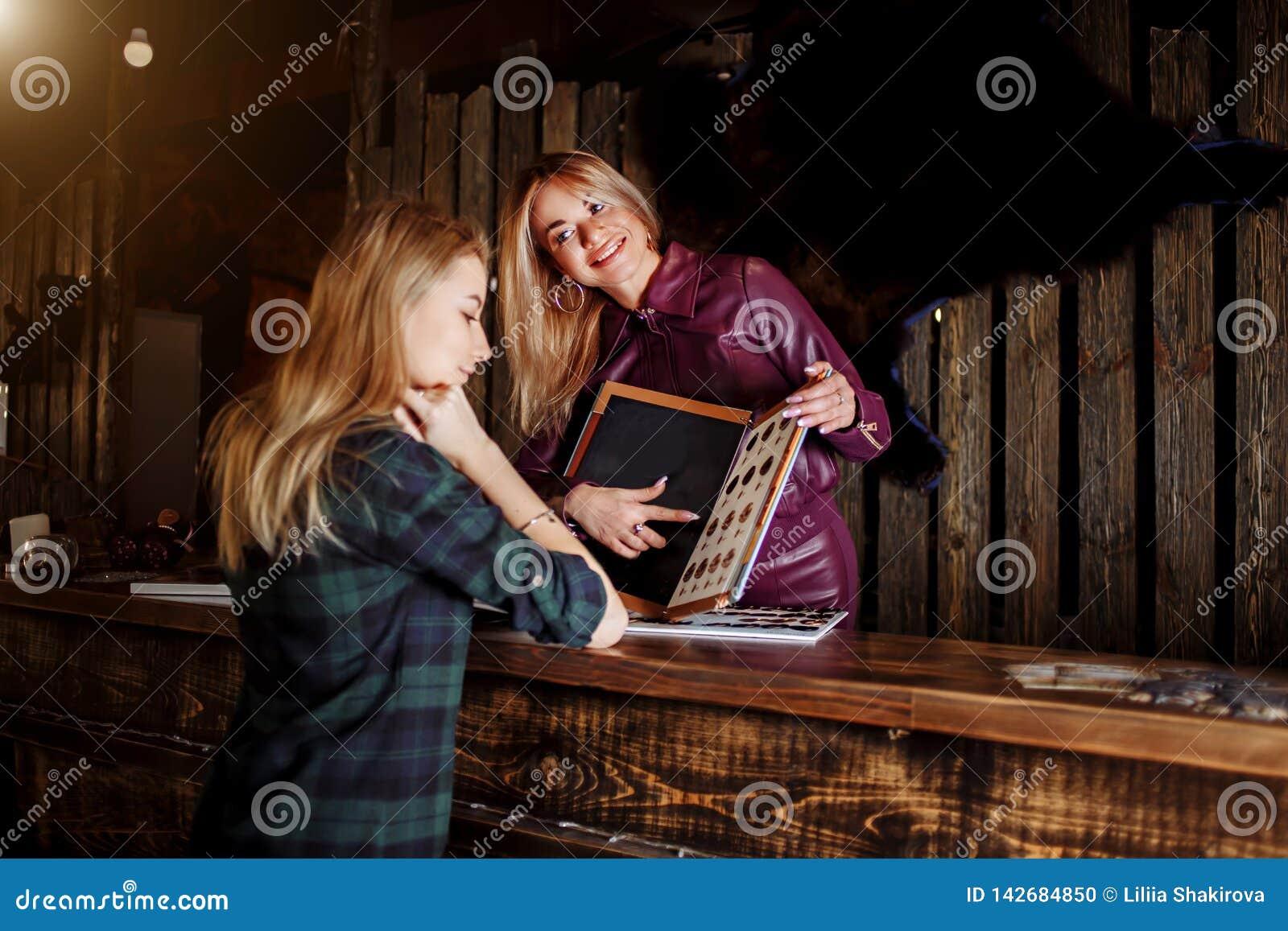 Bello amministratore femminile di bellezza e del salone di capelli con le manifestazioni di sorriso alla donna del listino prezzi