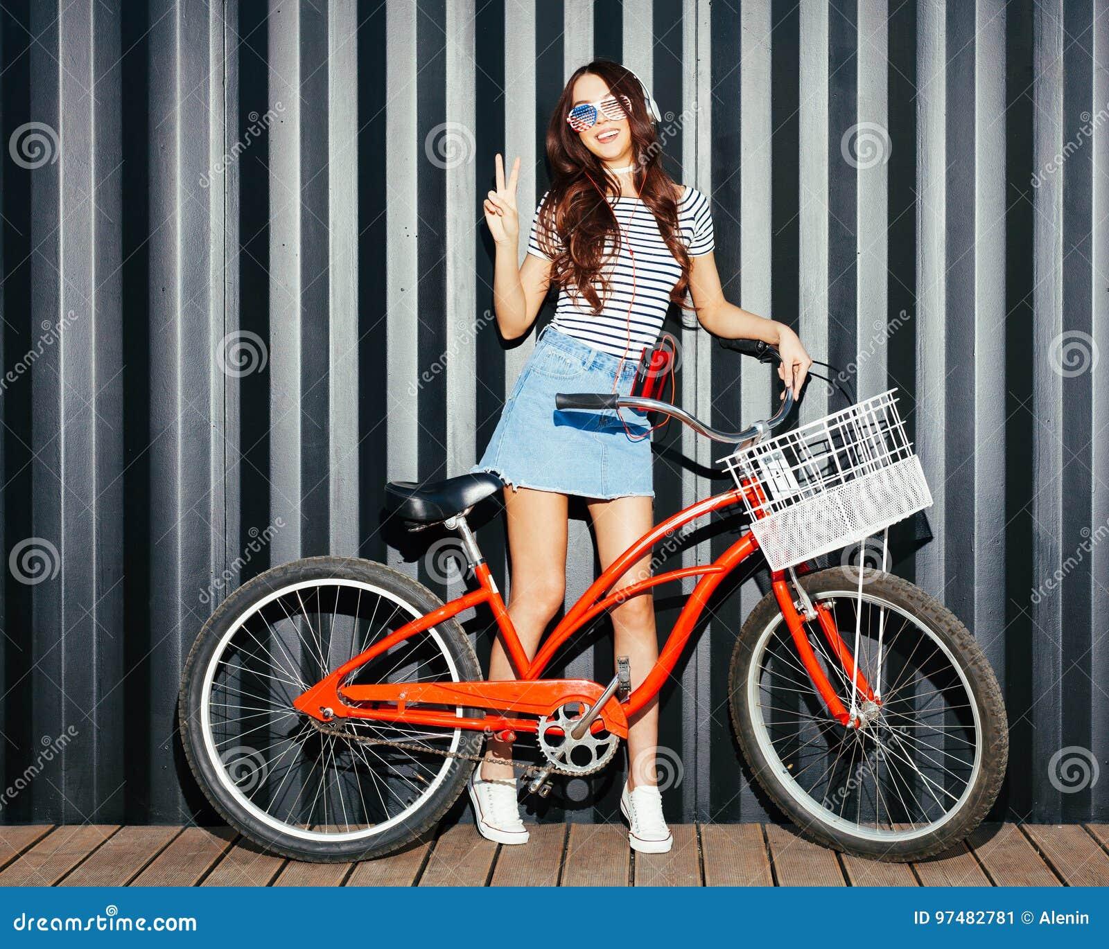 Bello asiatico con le gambe lunghe della ragazza in un attrezzatura di estate, negli occhiali da sole americani, in un giranastri