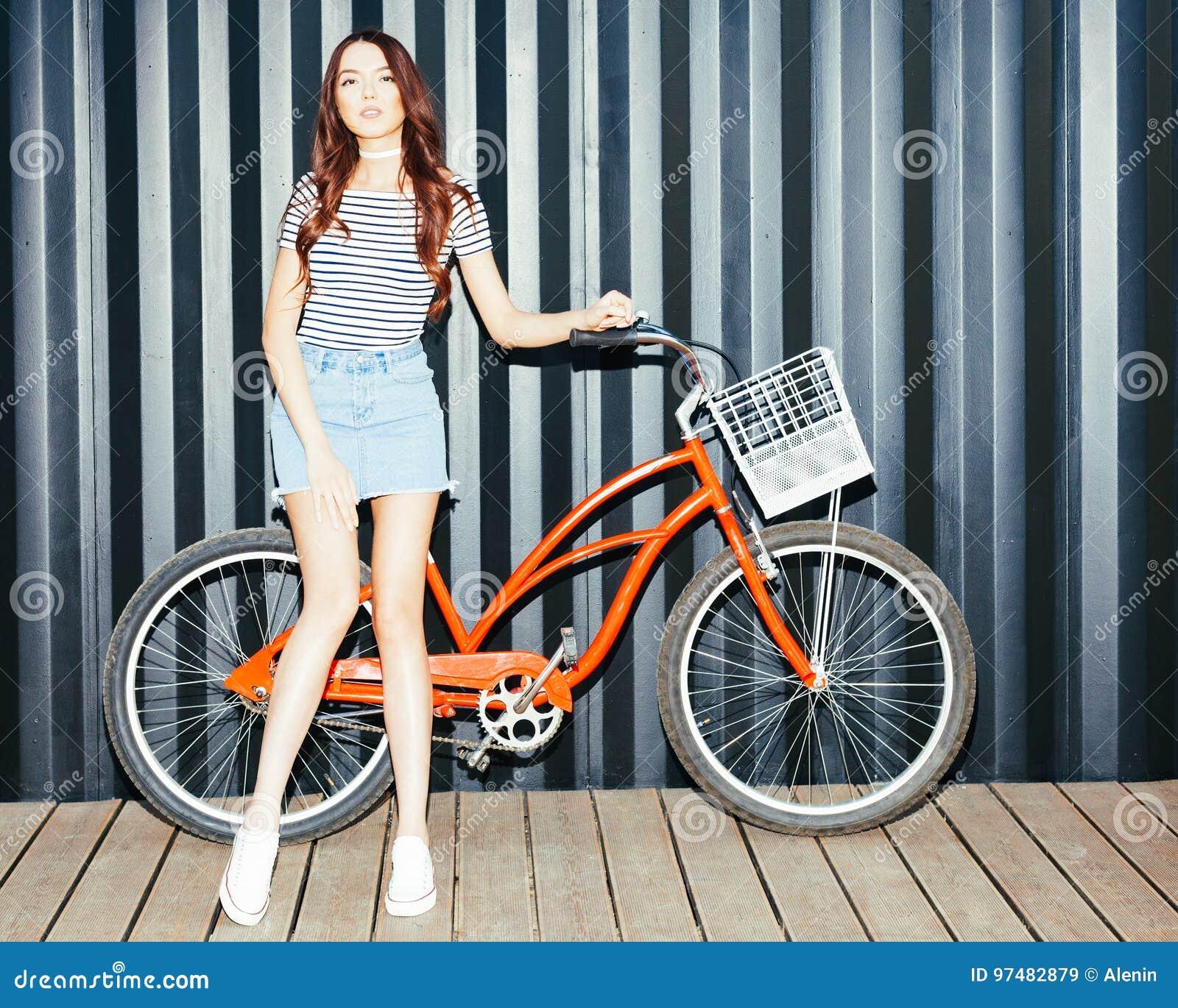 Bello asiatico dai capelli lunghi della ragazza in attrezzatura di estate che posa con una bicicletta rossa d annata Colpo di not