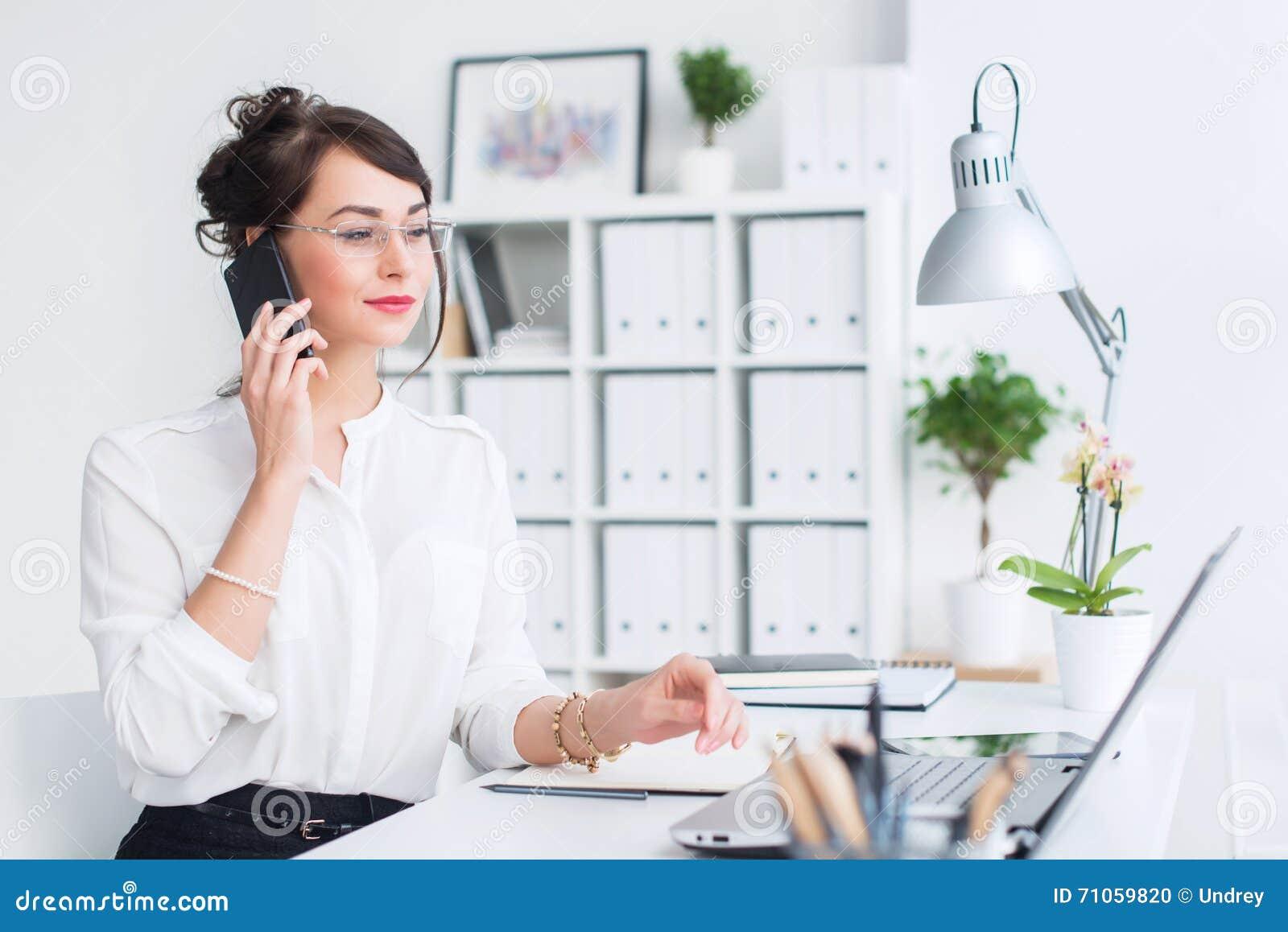 Bello assistente femminile che chiama facendo uso del cellulare Giovane impiegato di concetto che parla sul telefono cellulare ch