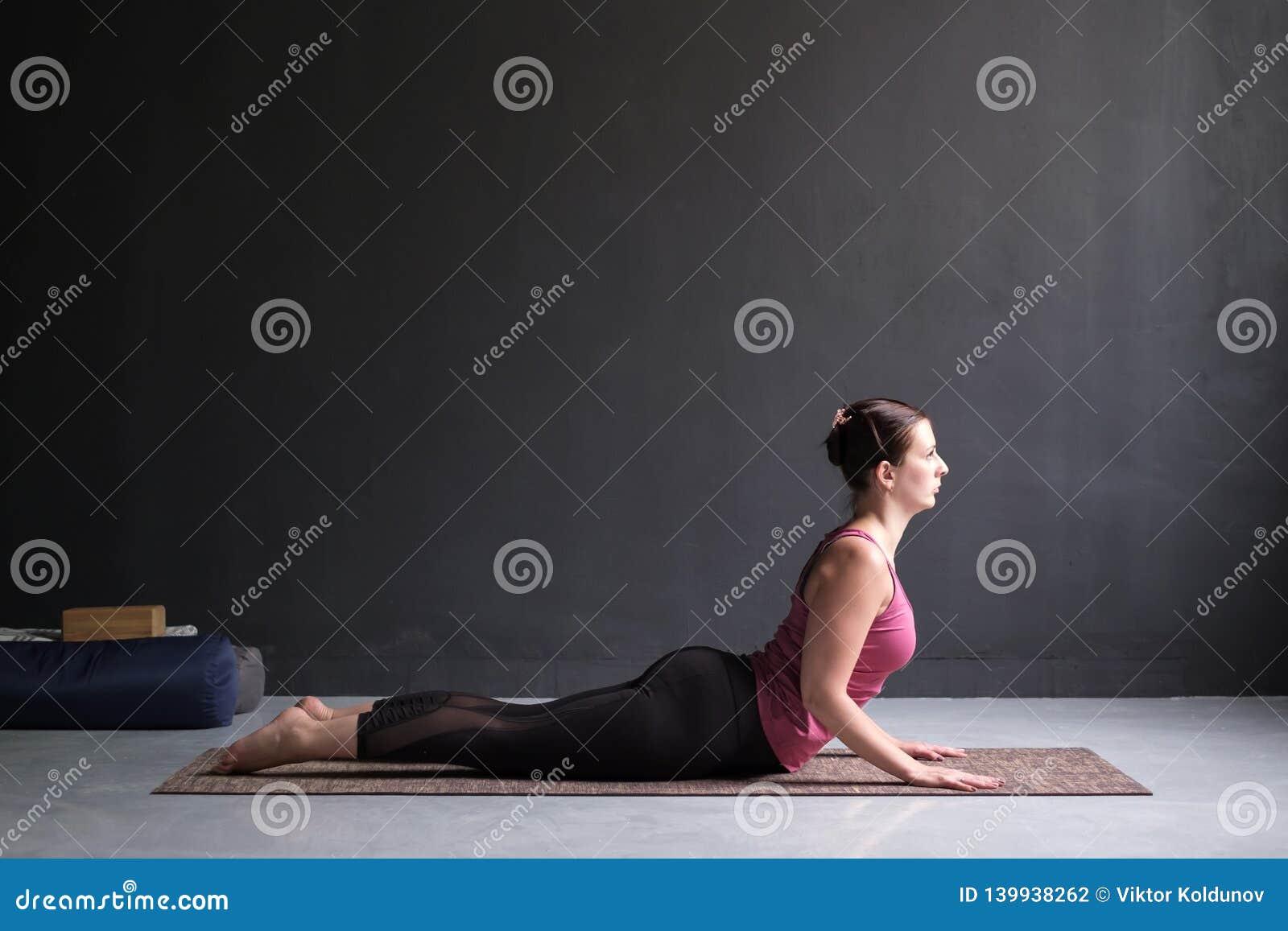 Bello bhujangasana adatto sportivo di asana di yoga di pratiche della donna di yogini