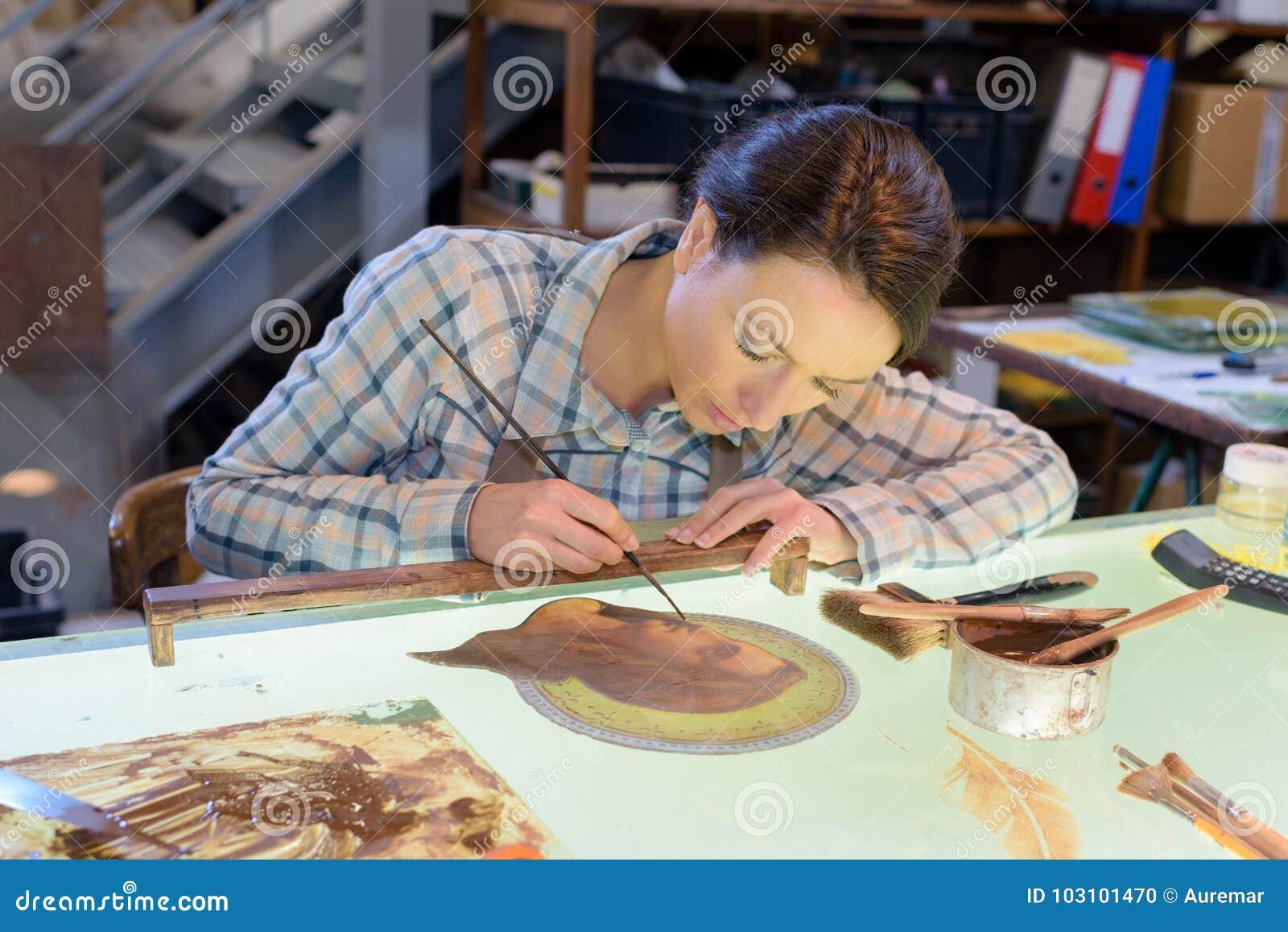 Bello craftswoman che assorbe officina