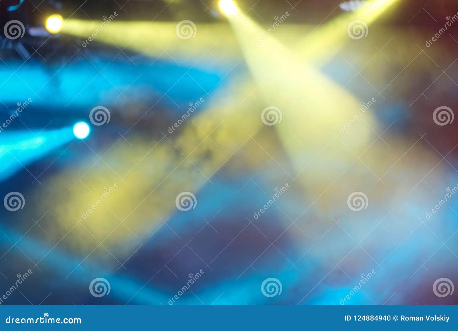 Bello fondo astratto dei raggi di luce multicolori luminosi Le luci gialle e blu di concerto splendono attraverso il fumo blurry