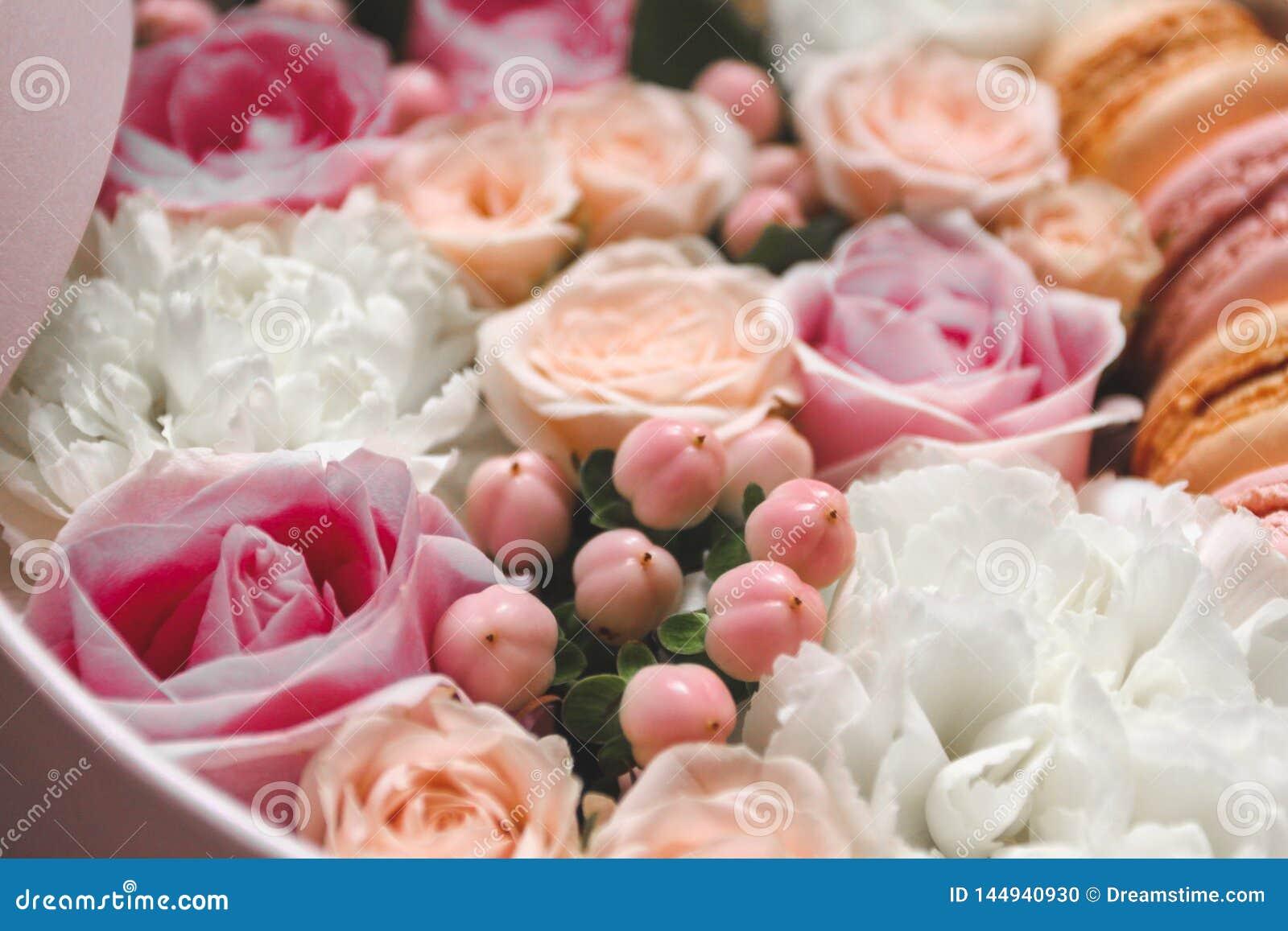 Bello fondo floreale nella scatola con i maccheroni sopra i precedenti