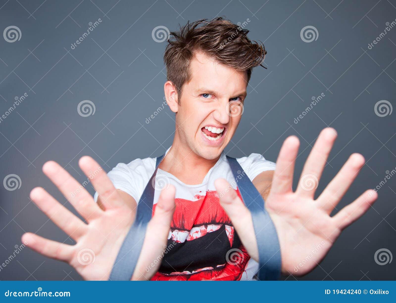 Bello giovane aggressivo con le parentesi graffe su gre