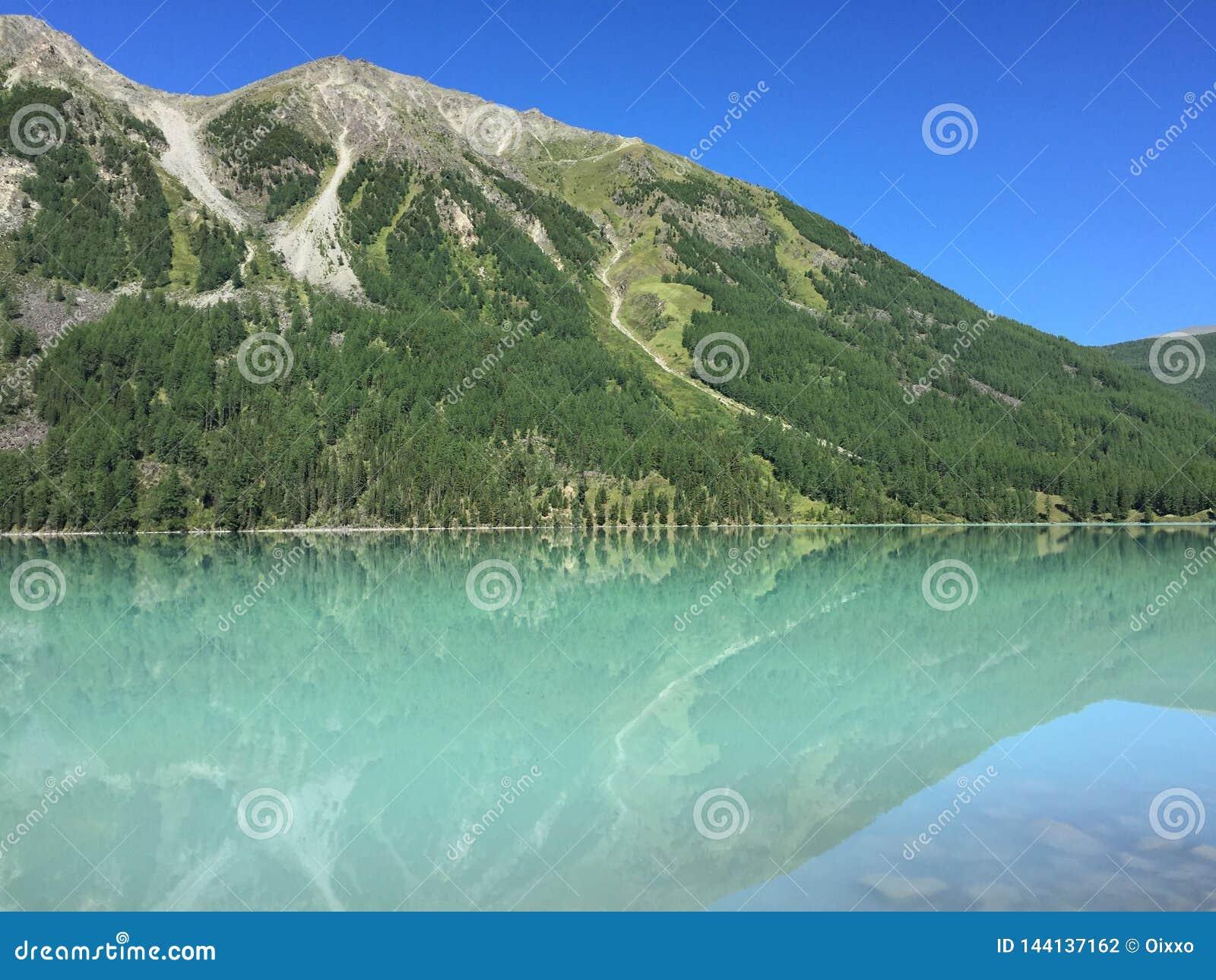 Bello lago Kucherla del turchese Riflessione delle montagne nell acqua Vacanze estive nelle montagne Immagine della freccia costi