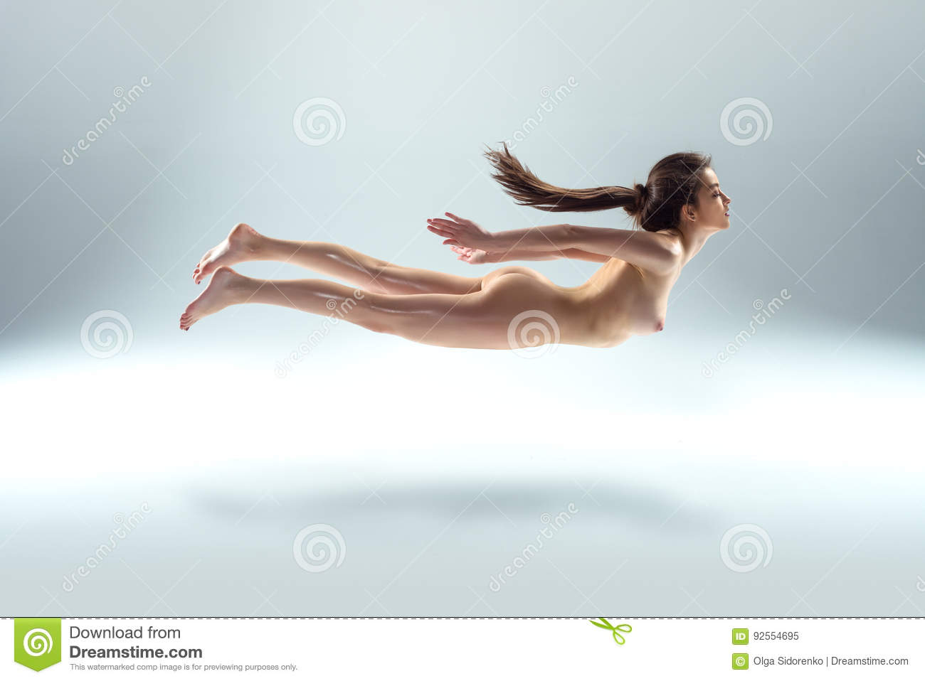 Bello levitare nudo della donna isolato su Gray Background