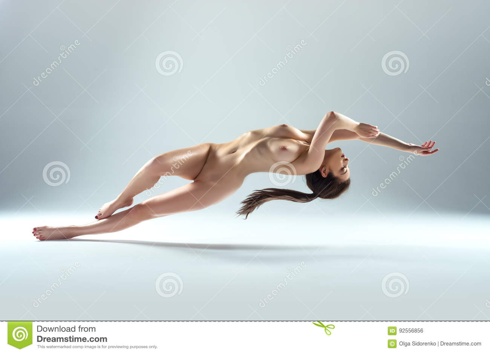 Bello levitare nudo della donna isolato su Gray Background
