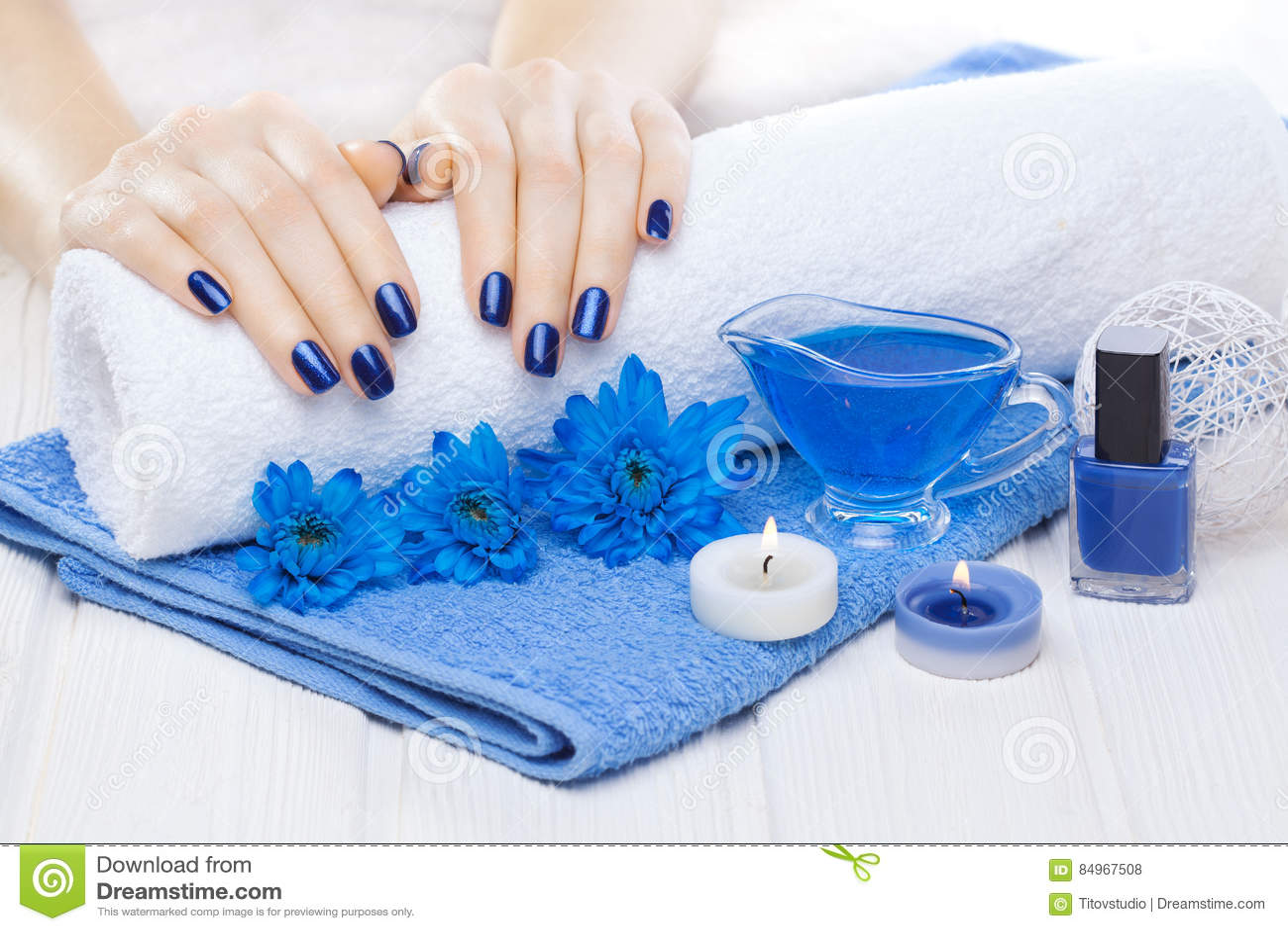 Bello manicure blu con il crisantemo ed asciugamano sulla tavola di legno bianca Stazione termale