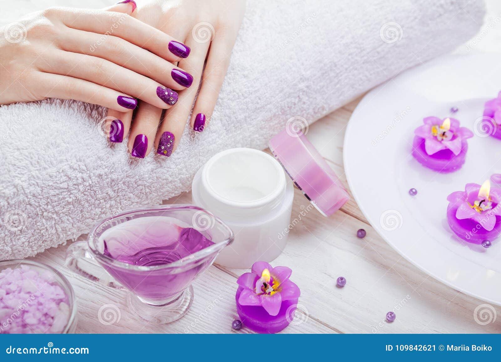 Bello manicure porpora con gli elementi essenziali della stazione termale