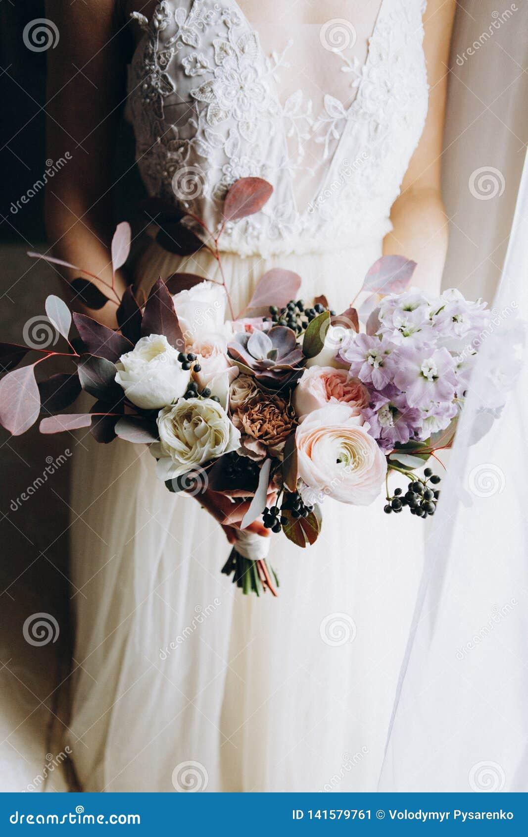 Bello mazzo bianco moderno e di rosa in mani delle spose Chiuda su del mazzo di nozze con differenti fiori