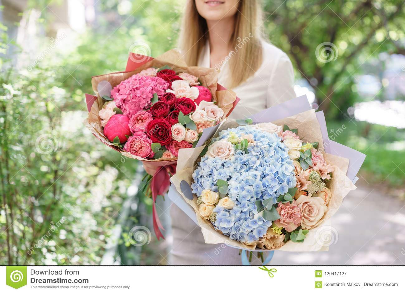 Bello mazzo di estate due Disposizione con i fiori della miscela Ragazza che tiene una disposizione dei fiori con l ortensia E