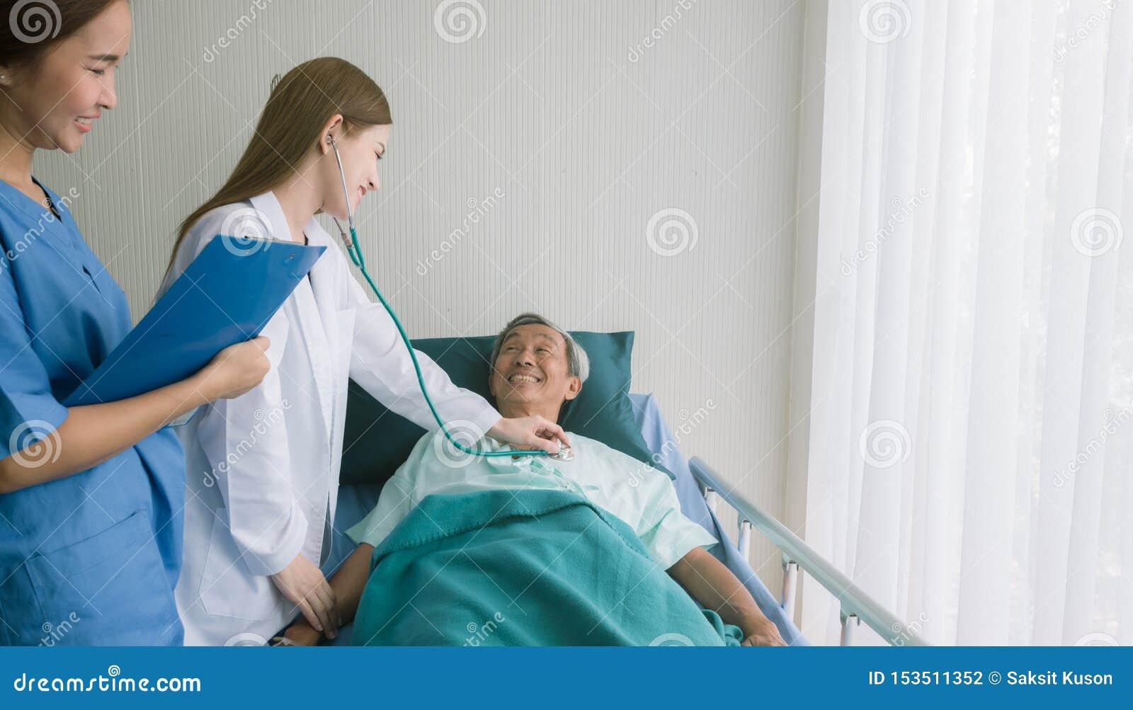 Bello medico asiatico ascolta il paziente di cuore nel letto di ospedale