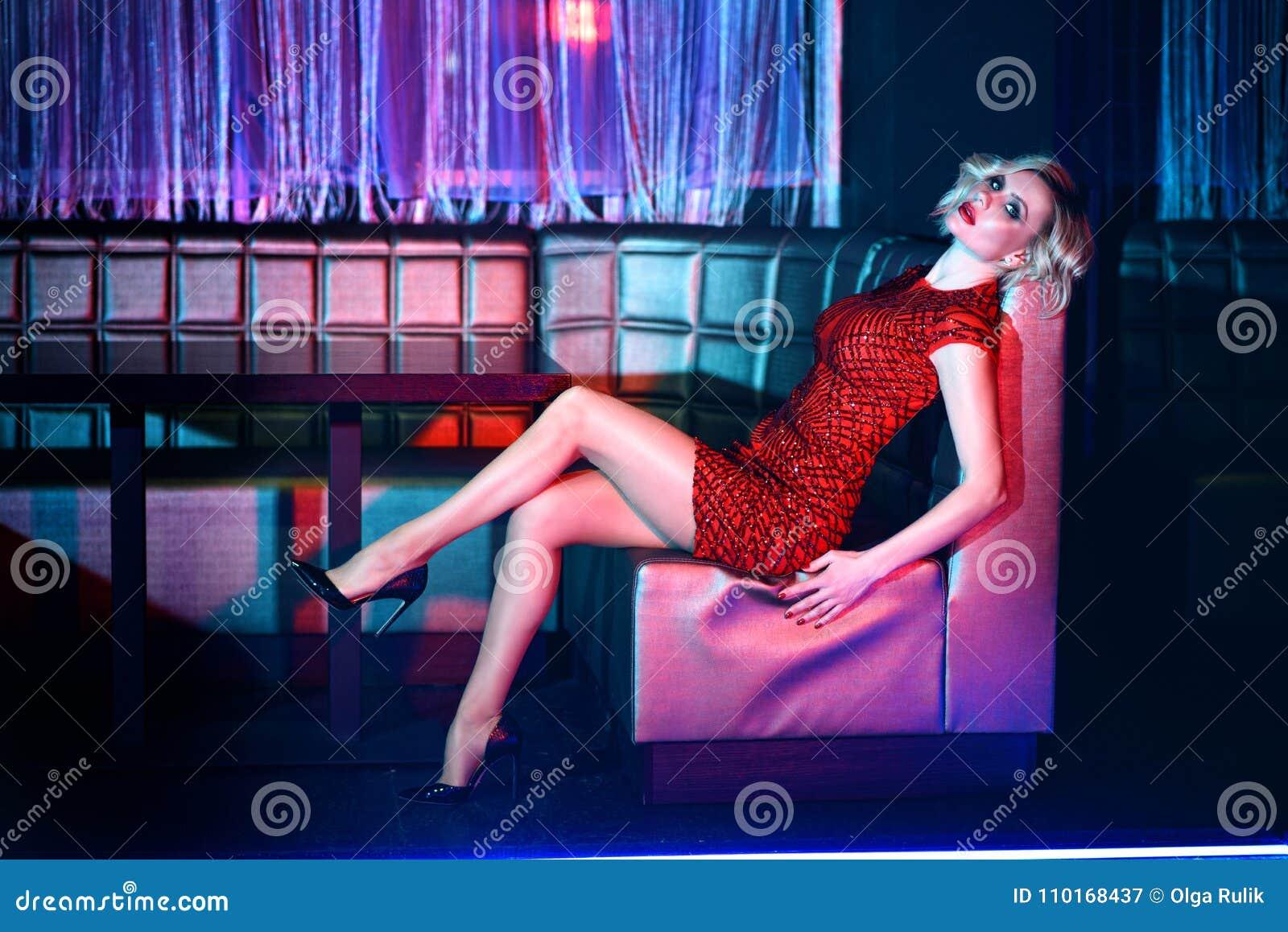 Bello modello biondo in breve vestito misura rosso dallo zecchino che si rilassa sul sofà quadrato in night-club